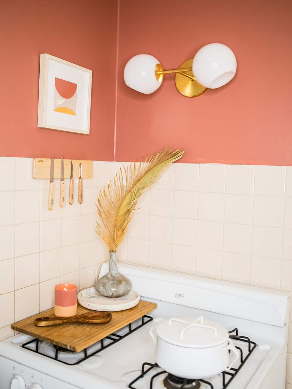 Newly finished stove corner with coral walls and a knife magnet.