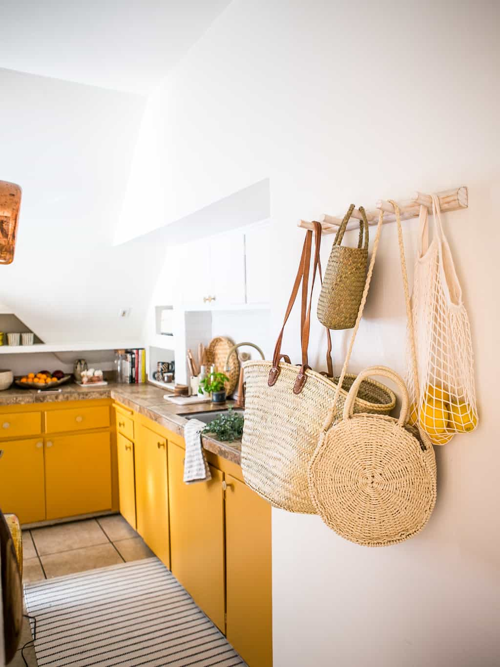 Newly finished kitchen with a rack of hanging baskets and yellow mustard cabinets.