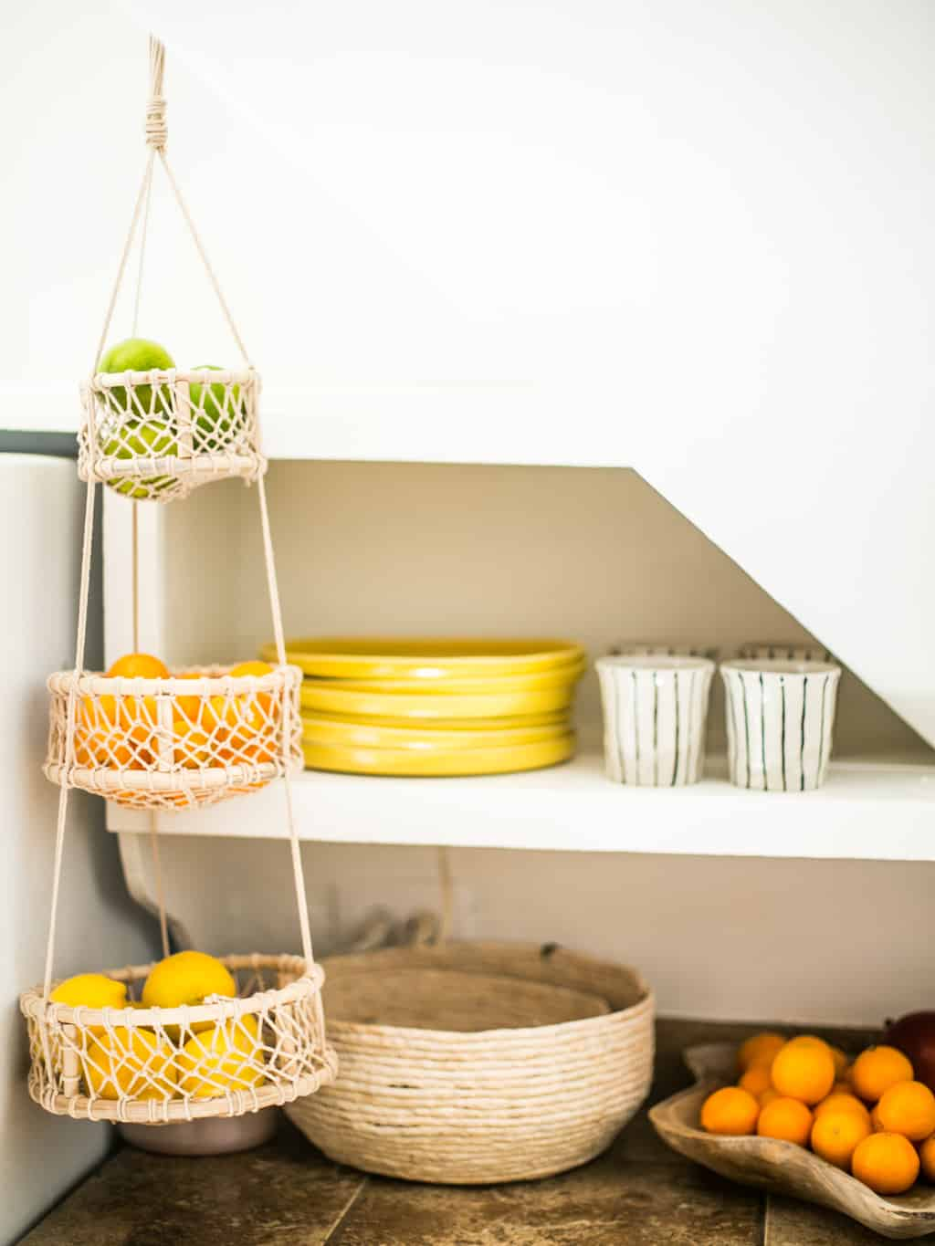 Corner of the kitchen with new yellow plates and coffee cups, with a hanging basket of fruit.
