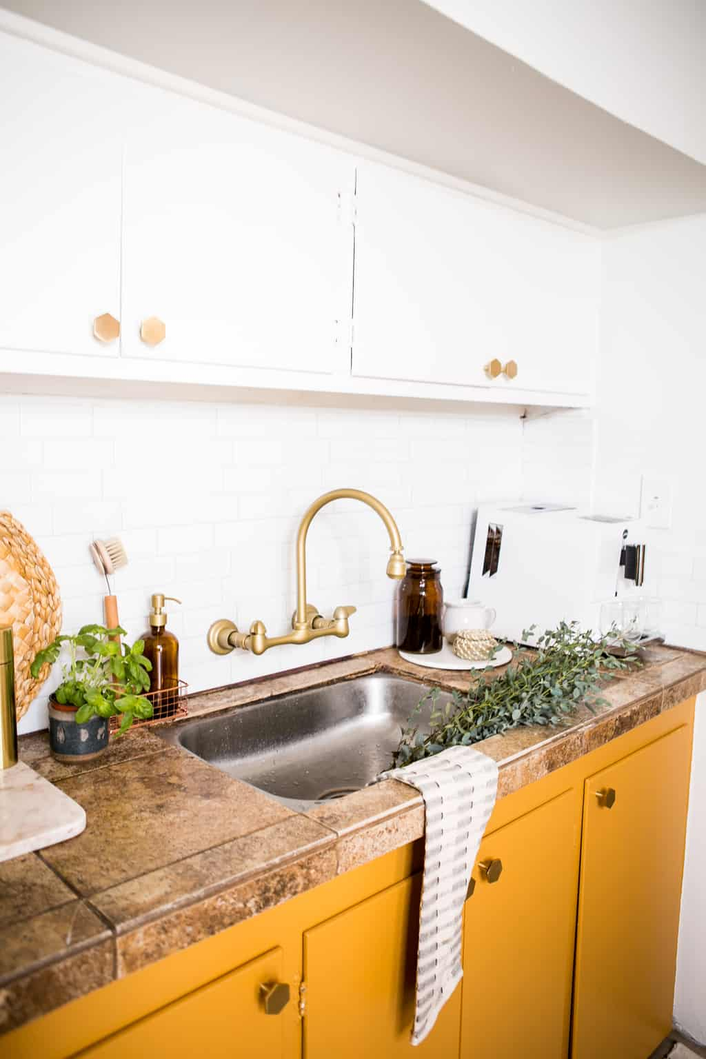 Gold faucet with newly painted yellow mustard cabinets with new gold hardware.