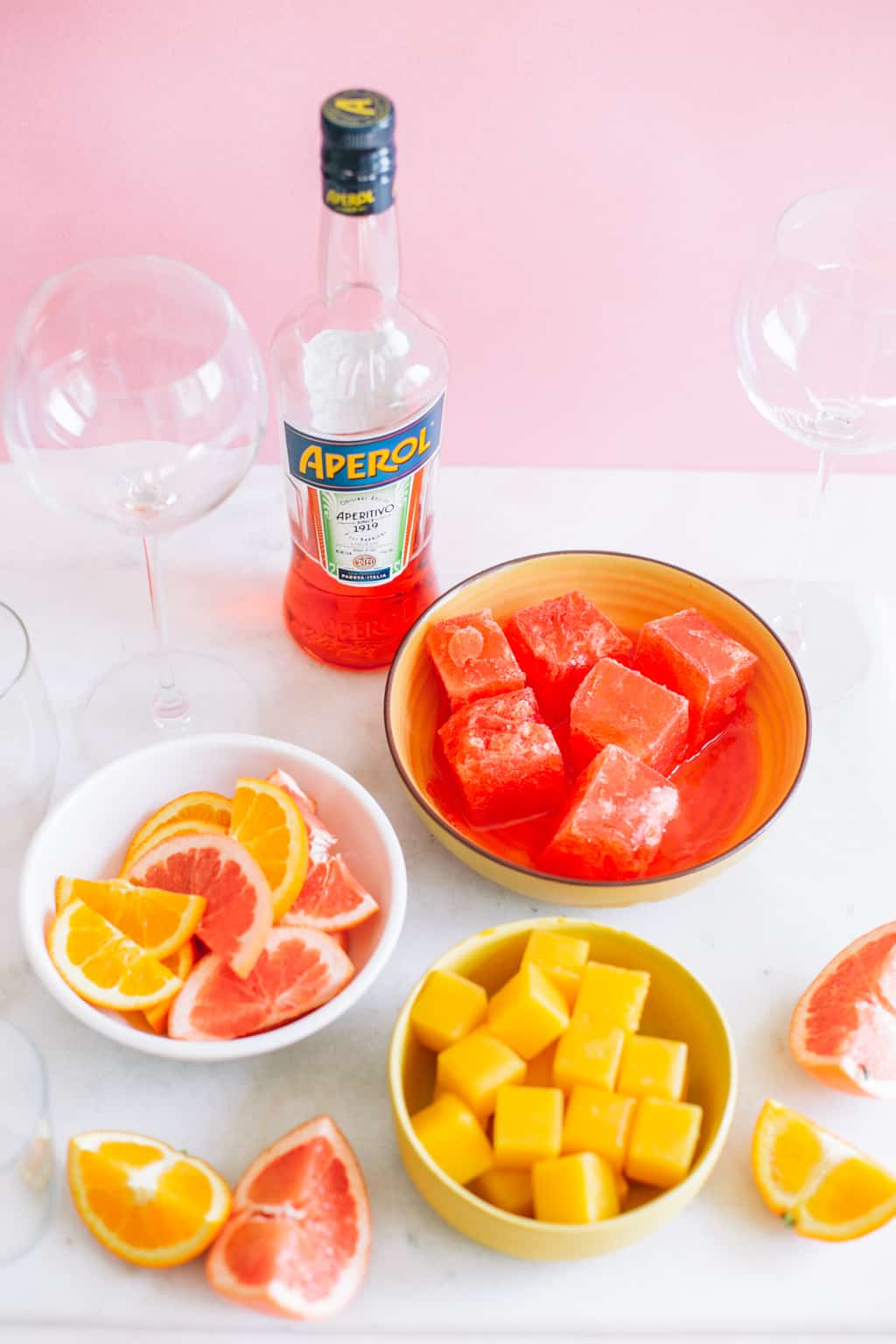 frozen orange juice and aperol ice cubes in two bowls with citrus slices and aperol bottle