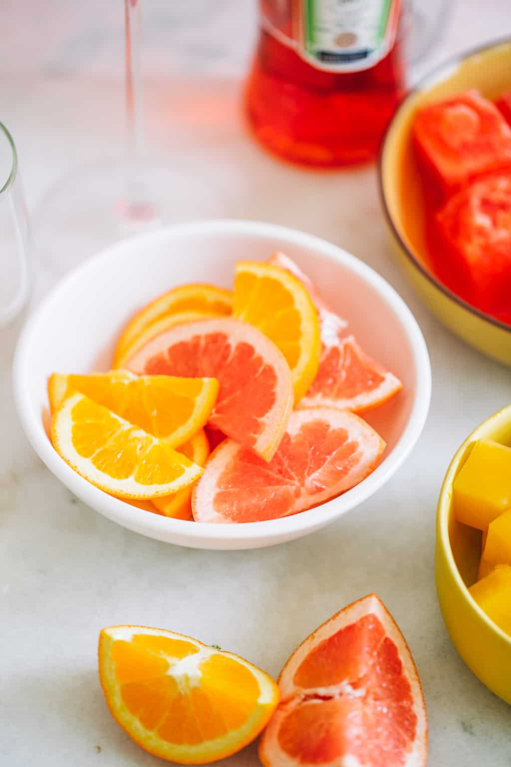 A bowl or orange and grapefruit citrus wedges.