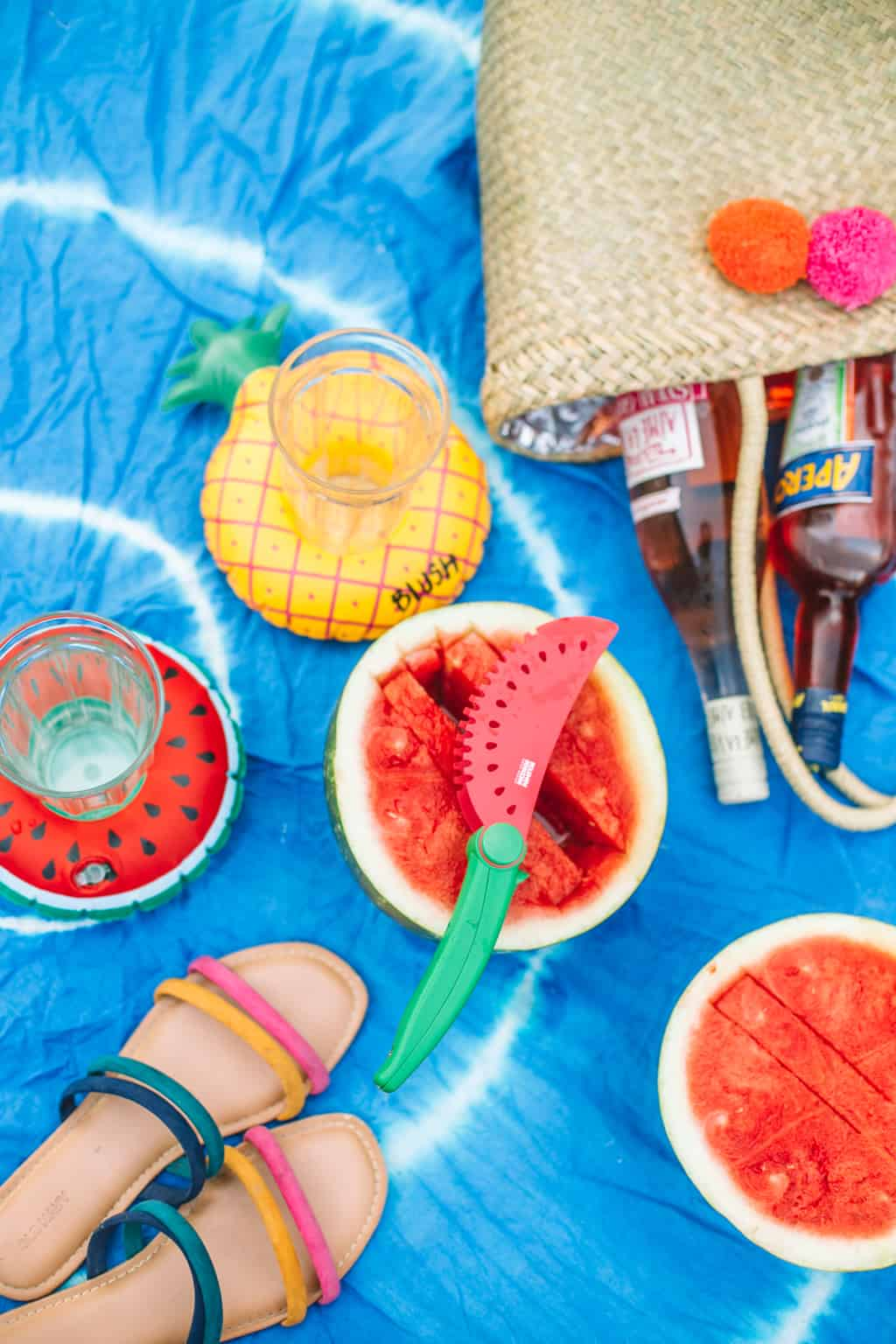 Blue tye dye beach blanket topped with sandals, watermelon and a beach bag.