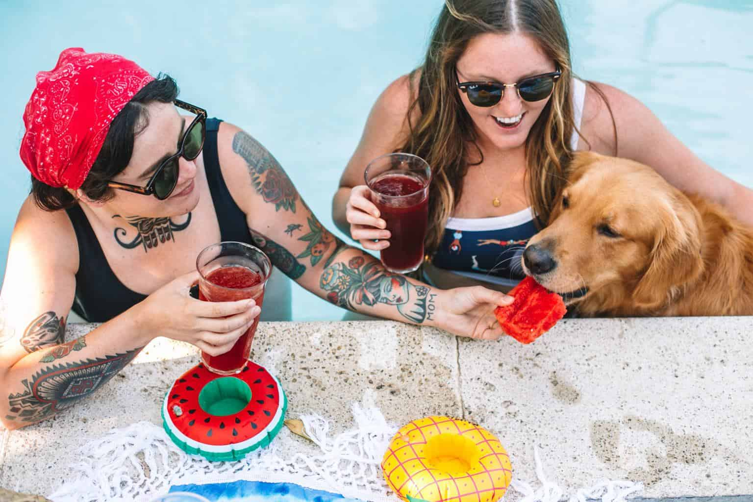 Two girls inside of a swimming pool feeding a dog a piece of watermelon.