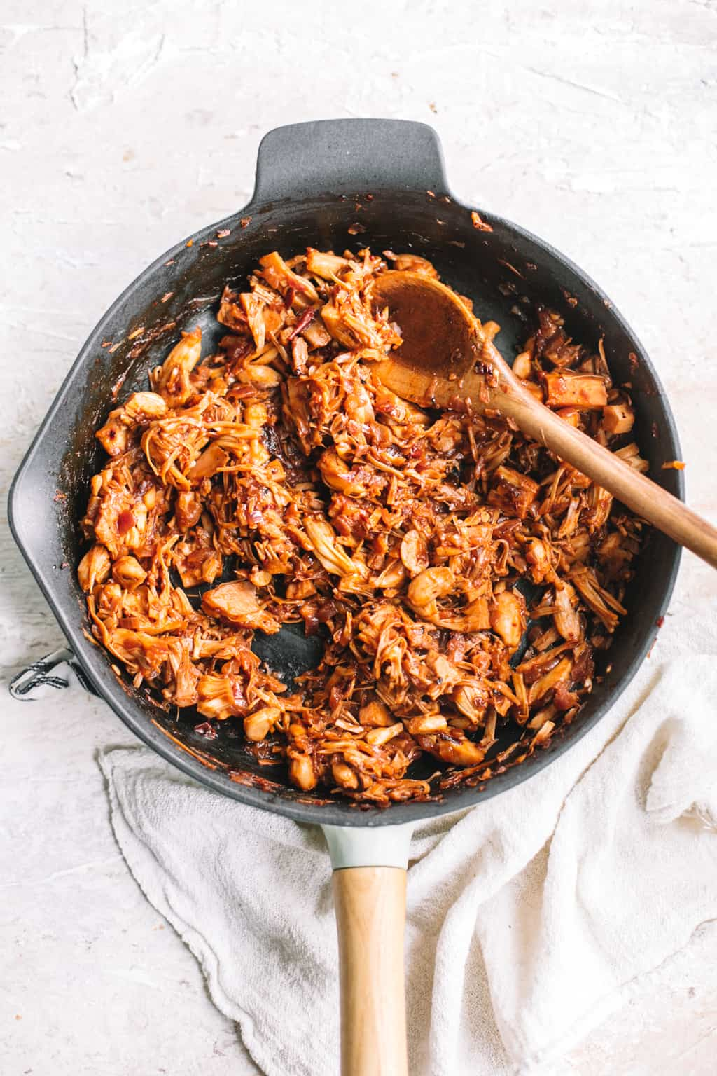 Mexican chipotle BBQ jackfruit taco filling in cast iron skillet with wooden spoon