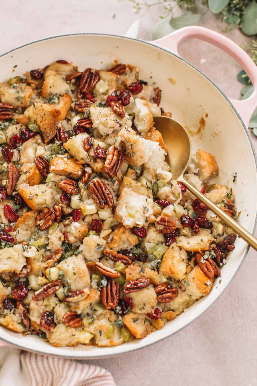 easy apple stuffing with pecans in pink casserole dish with gold serving spoon