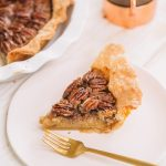slice of pecan pie with homemade pie crust on white plate with gold fork
