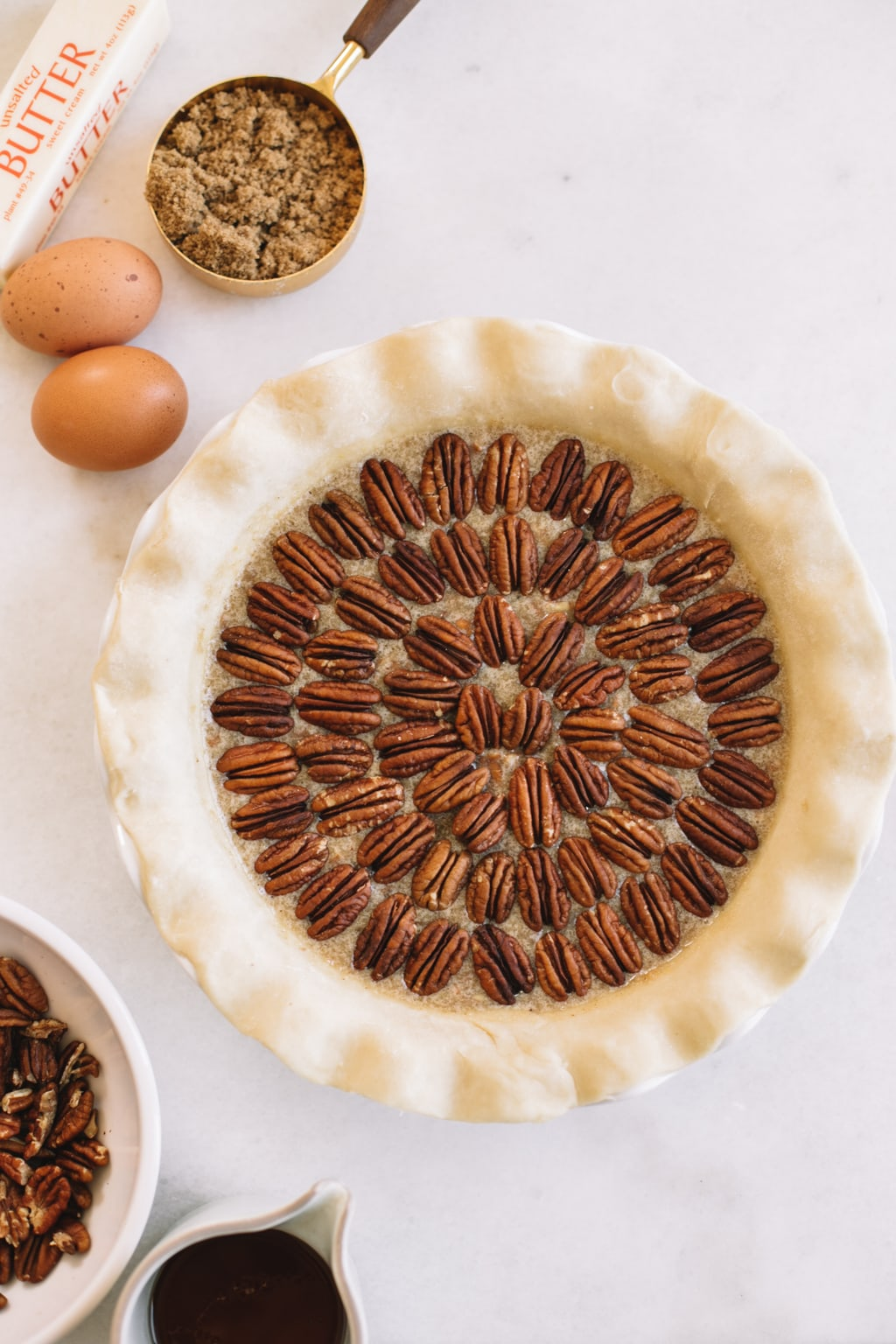 pecans placed in concentric circles in homemade pie crust in white pie dish with two eggs on the side