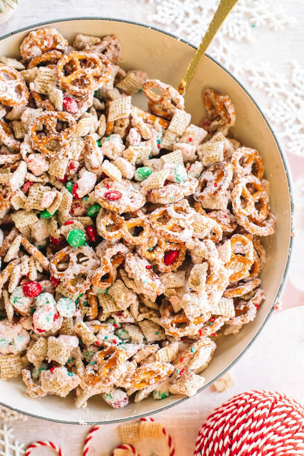 white chocolate chex mix recipe in large bowl with spoon and Christmas ribbon