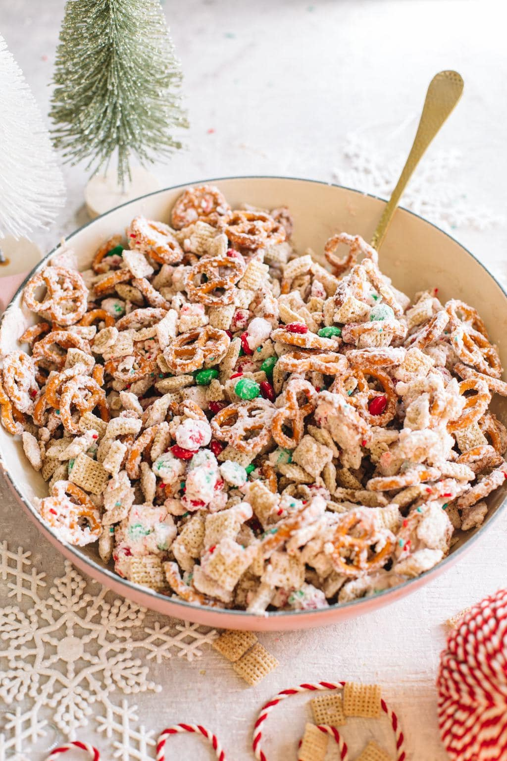 easy white chocolate snack mix recipe in large bowl with spoon and Christmas ribbon