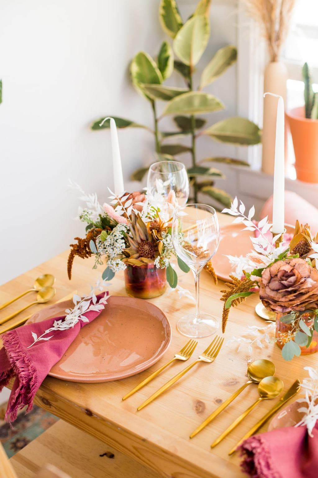 Thanksgiving table setting with a peach plate and gold flatware.