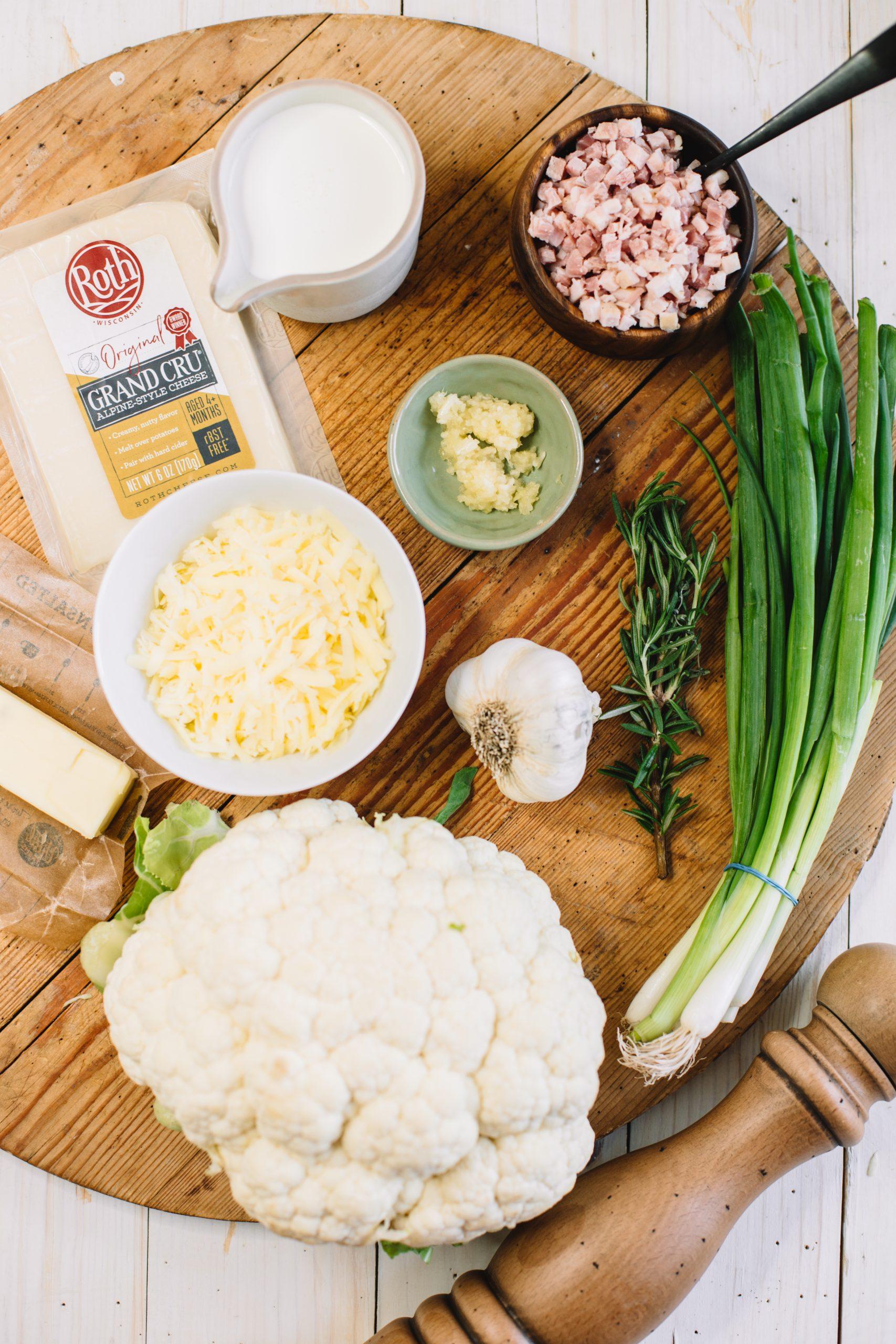 cauliflower, shredded cheese, garlic, rosemary, scallions, pancetta, cream, butter on wooden cutting board