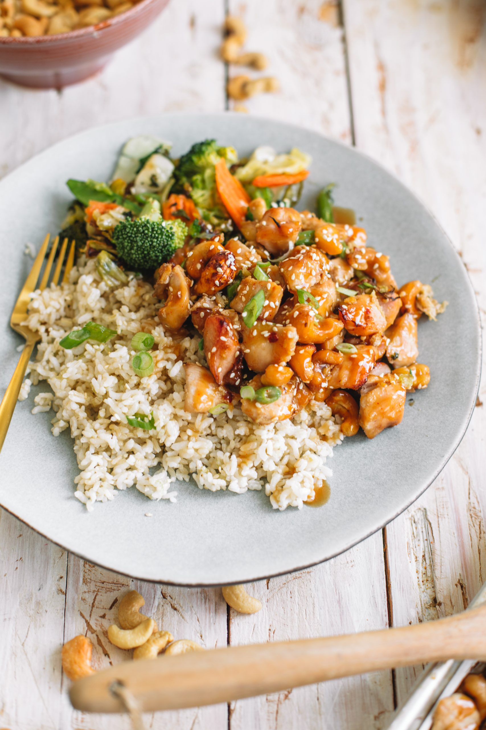 A blue plate of cashew chicken, asian style vegetables and brown rice.