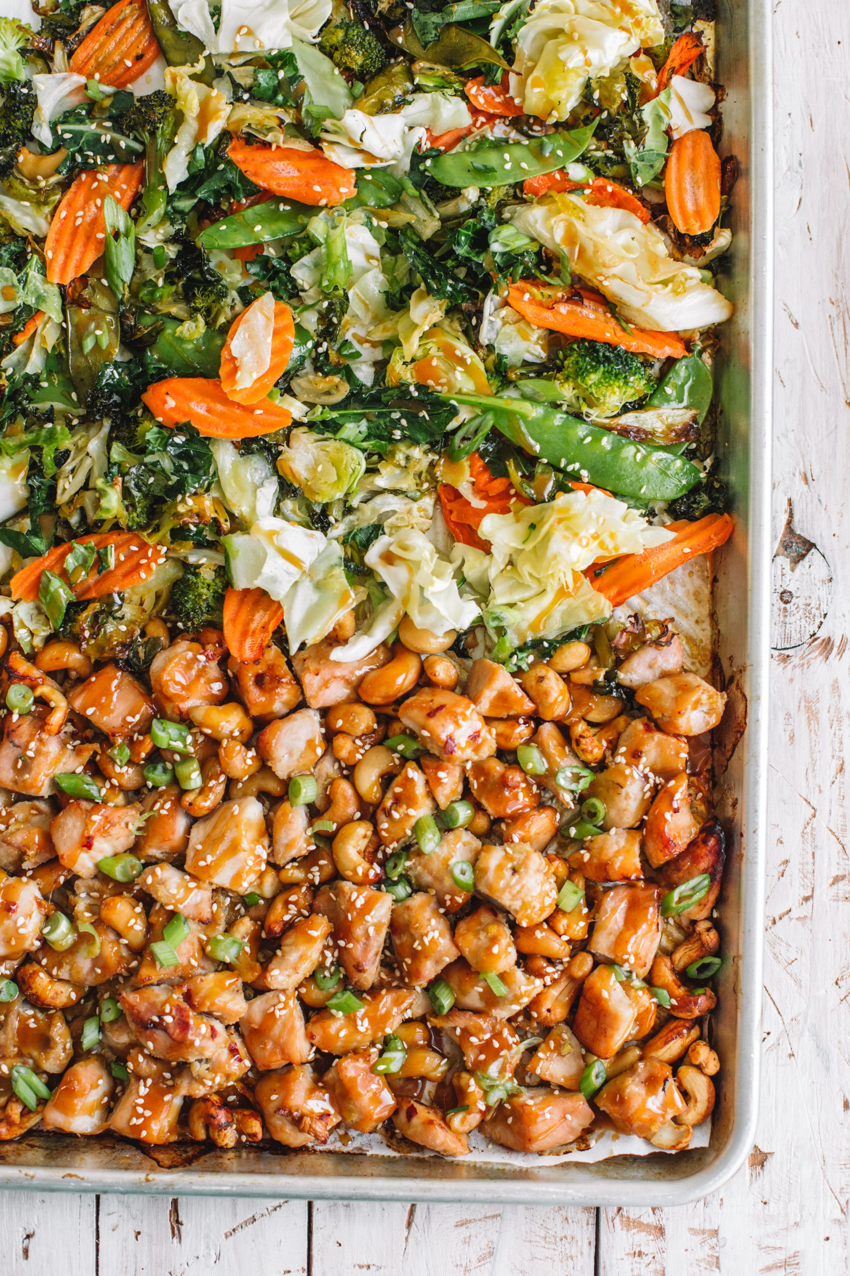 A sheet pan baking tray filled with baked cashew chicken and asian vegetables.