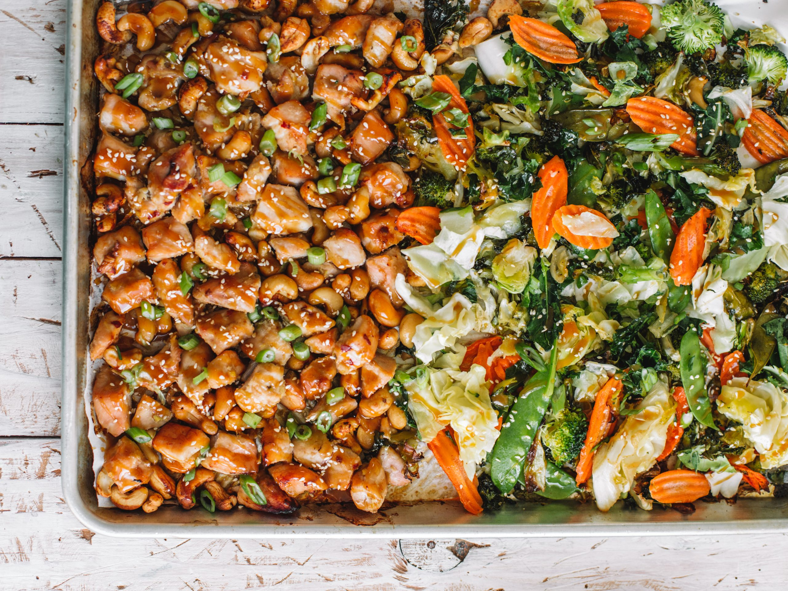 Sheet pan baking tray of cashew chicken and asian vegetables.