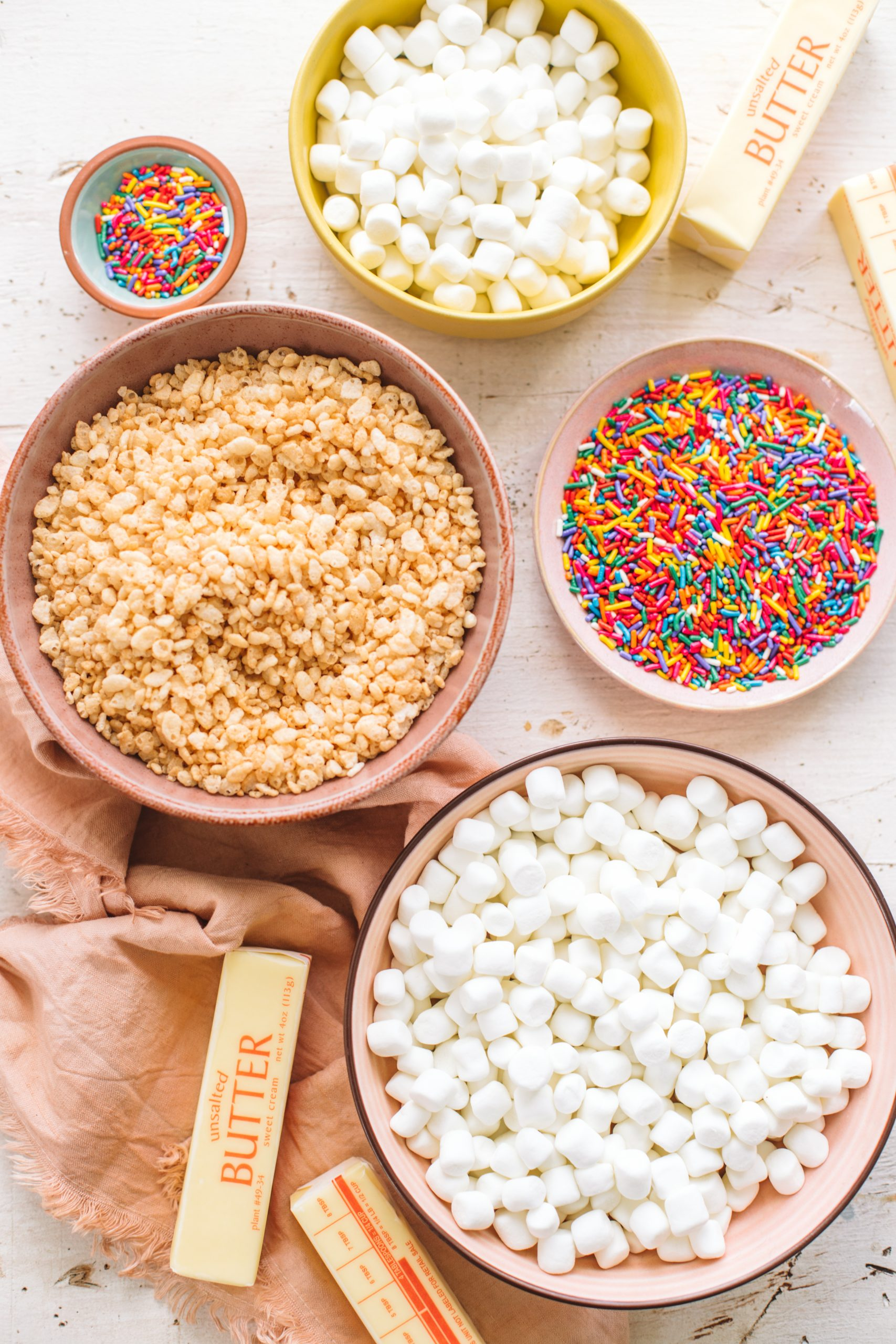 Bowls of marshmallows, rice krispies, sprinkles and butter.