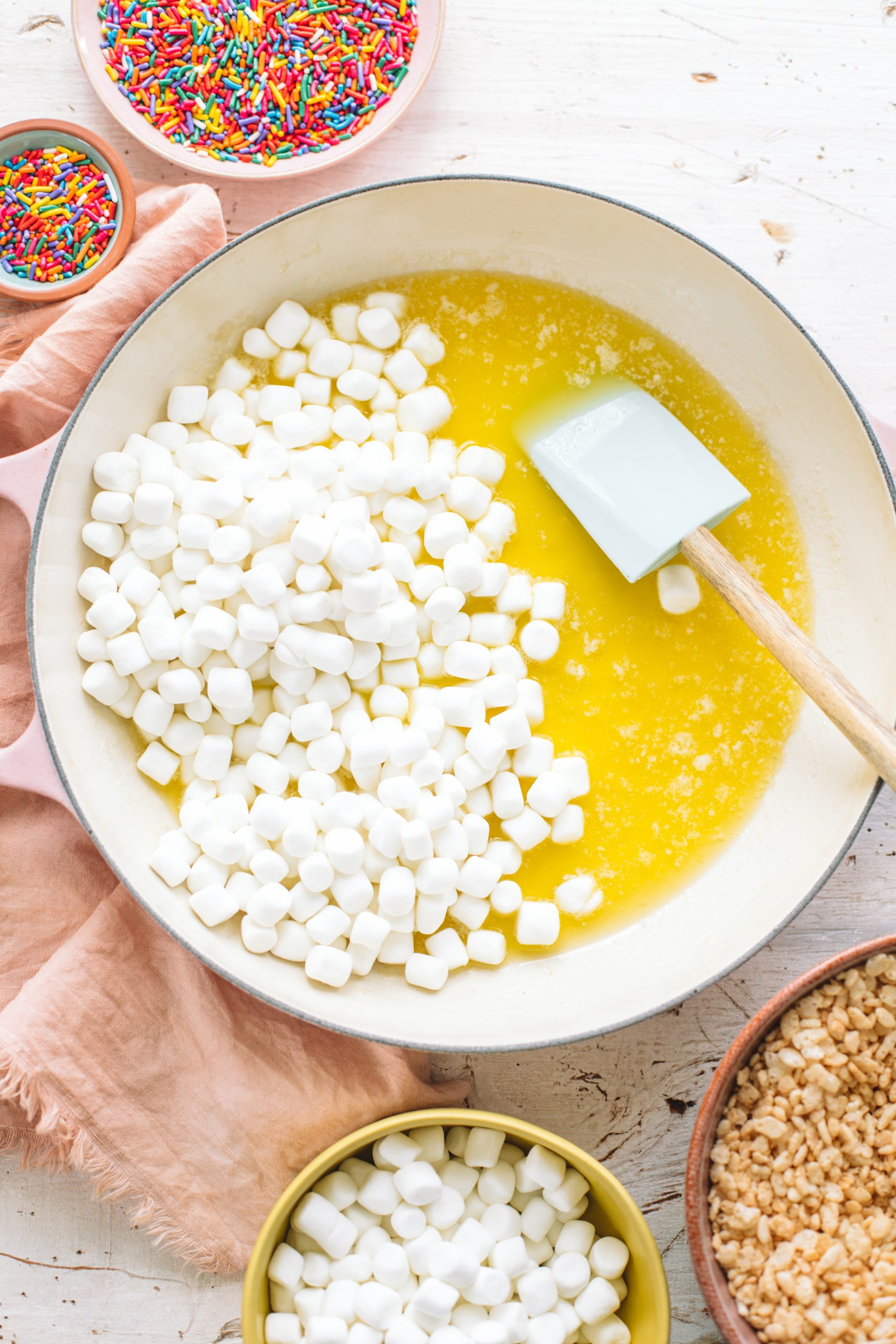 A shallow braiser dish filled with melted butter and marshmallows.