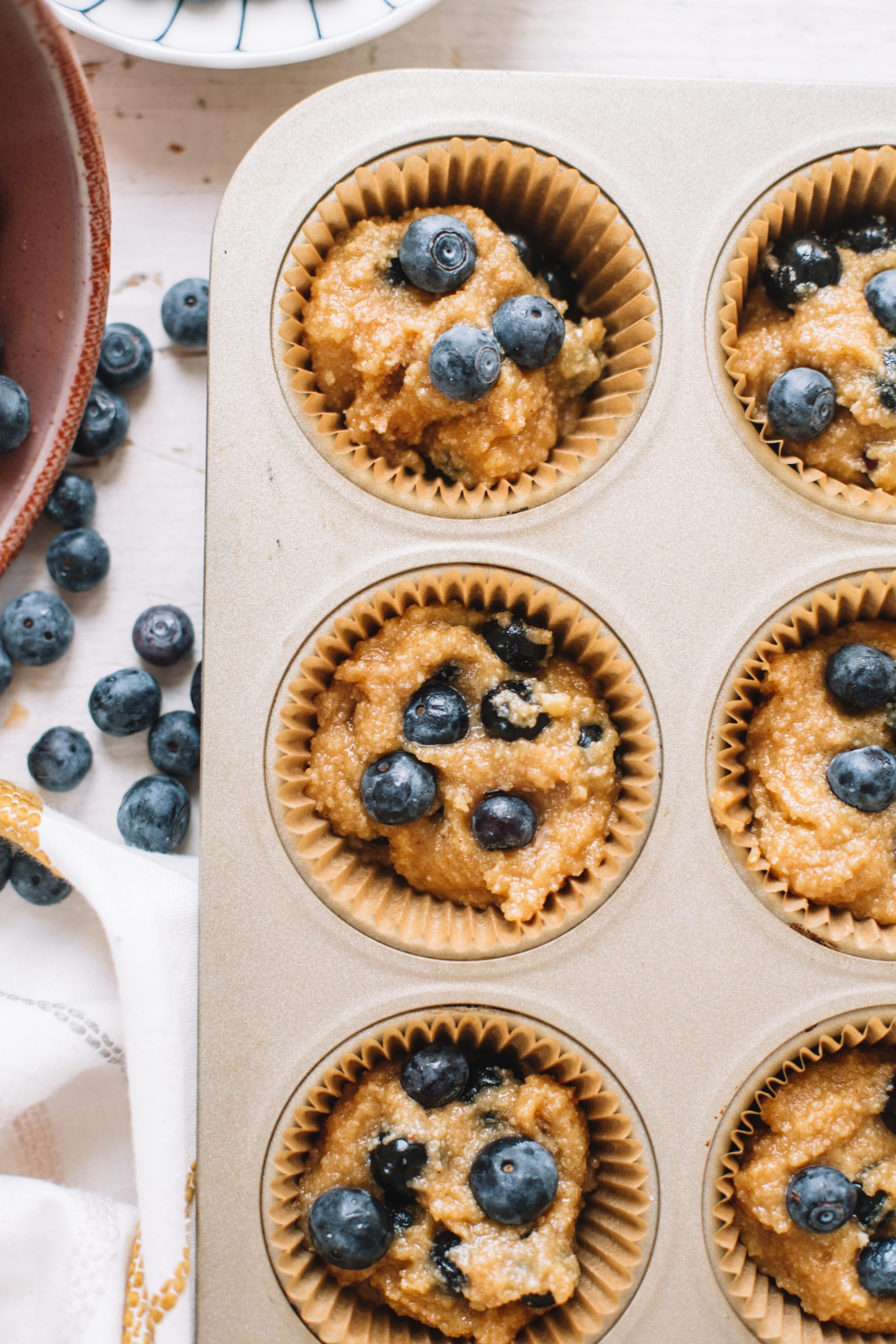 Blueberry muffin batter scooped into cupcake tin.