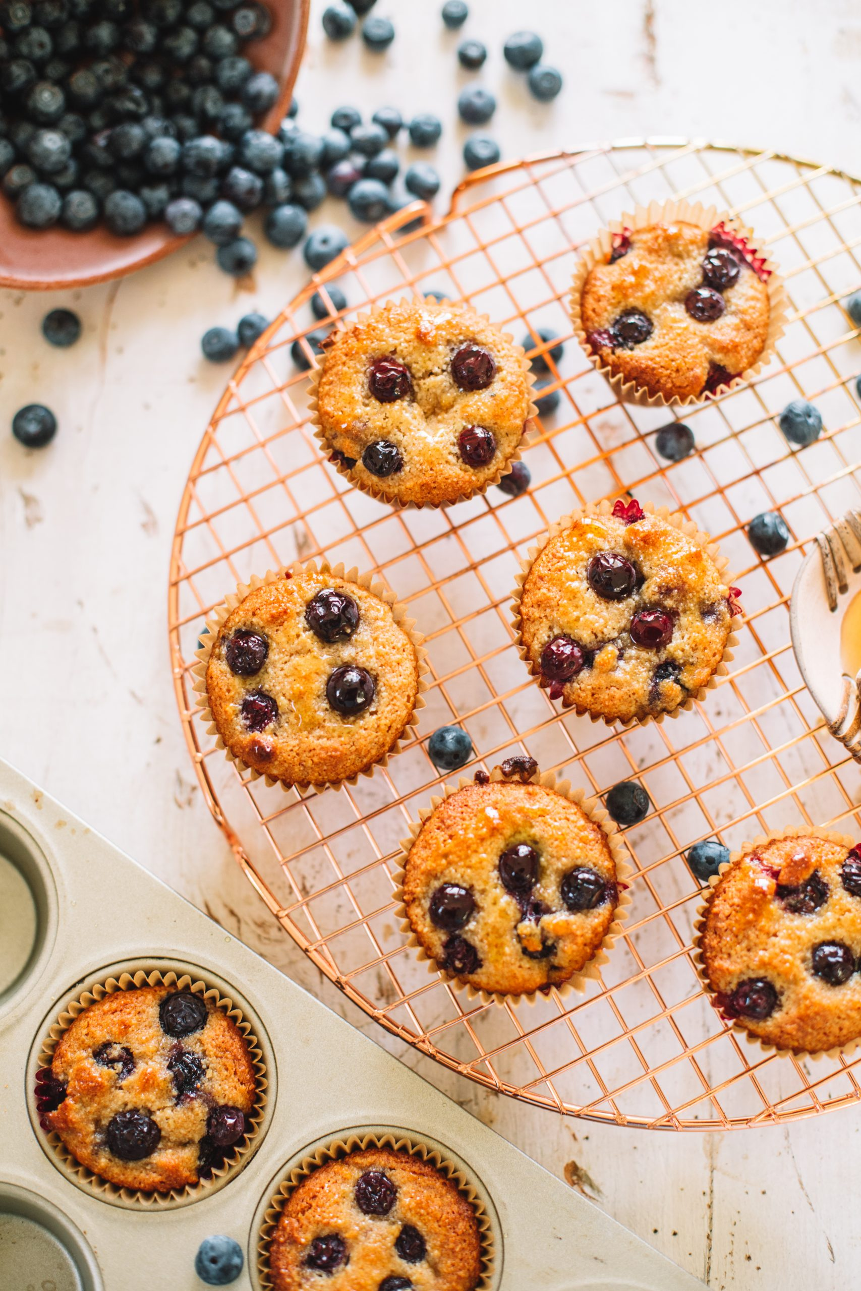 Baked blueberry muffins cooling on a copper cooling rack.