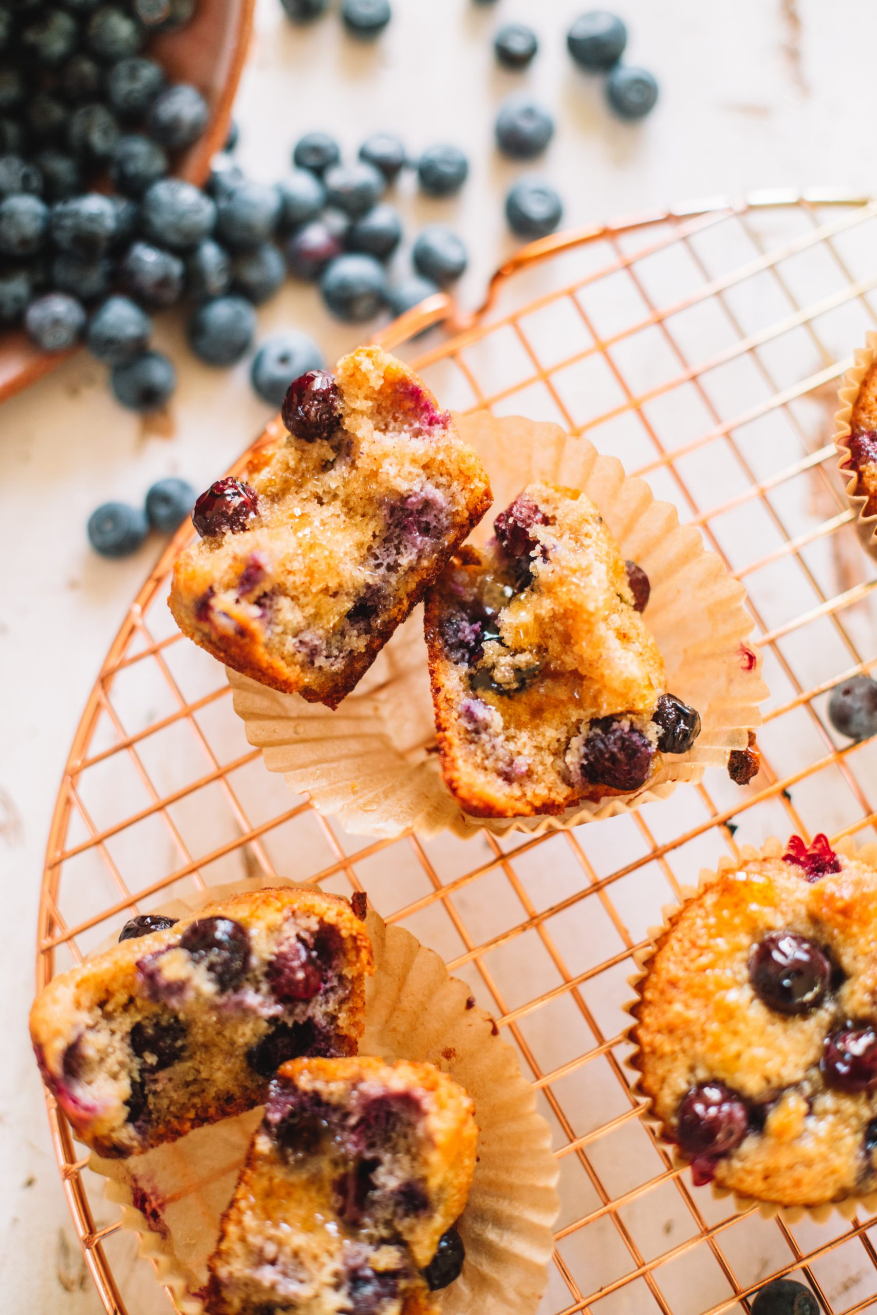A fresh healthy blueberry muffin broke in half on a copper cooling rack.