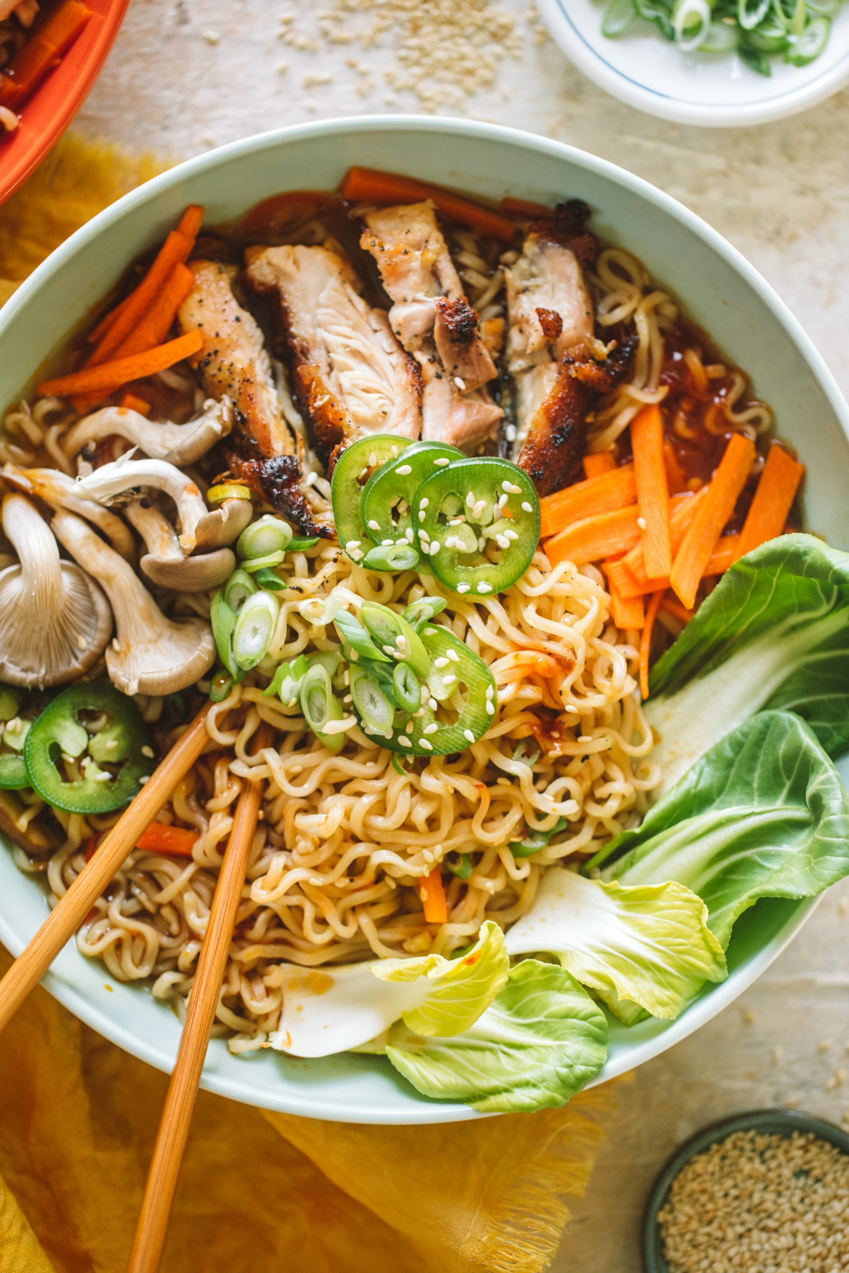 Spicy chicken ramen topped with jalapenos, mushrooms, bok choy, carrots and served in a blue bowl.