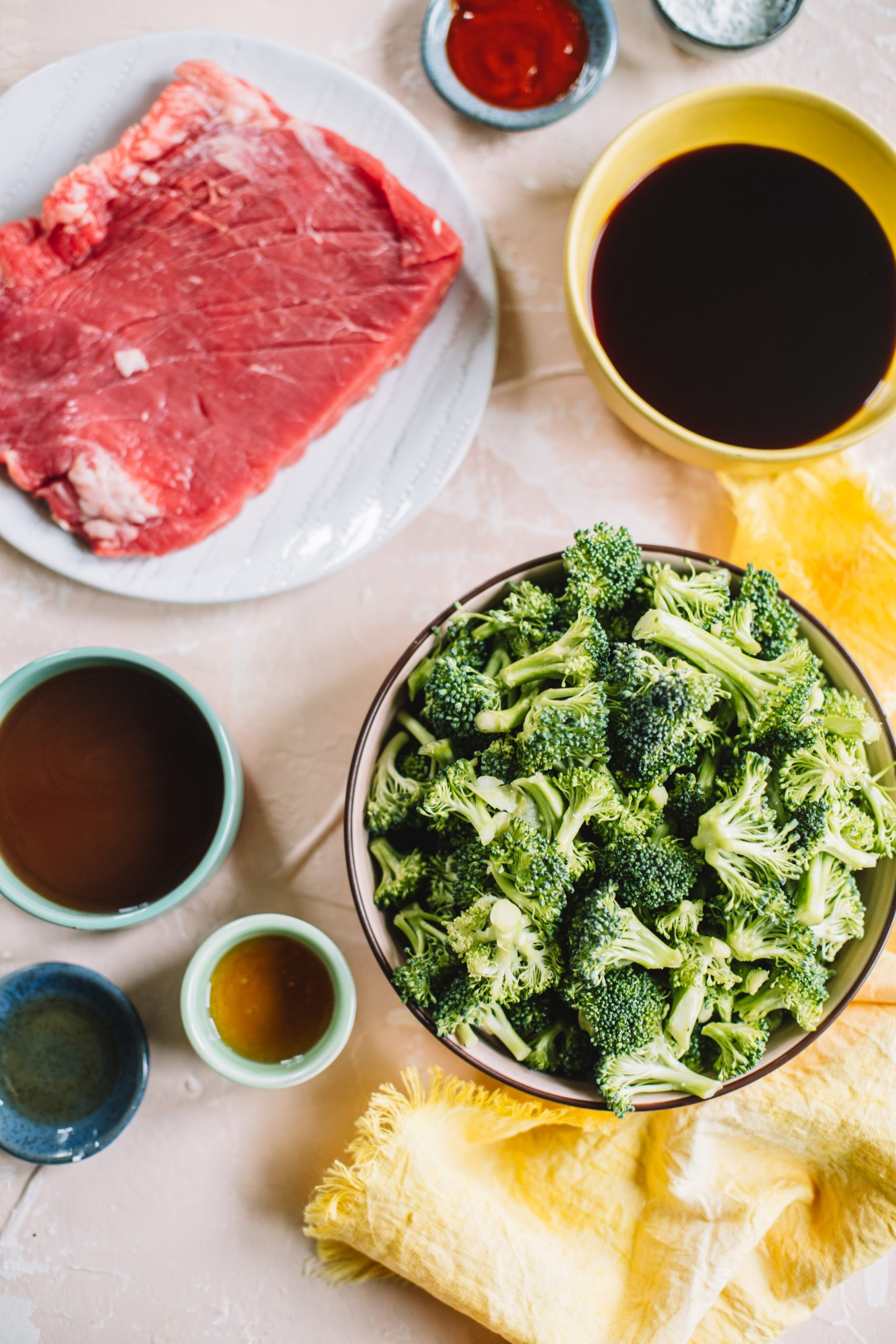 Flank steak, bowl of broccoli, soy sauce, sriracha, honey, sesame oil and beef broth bowls.