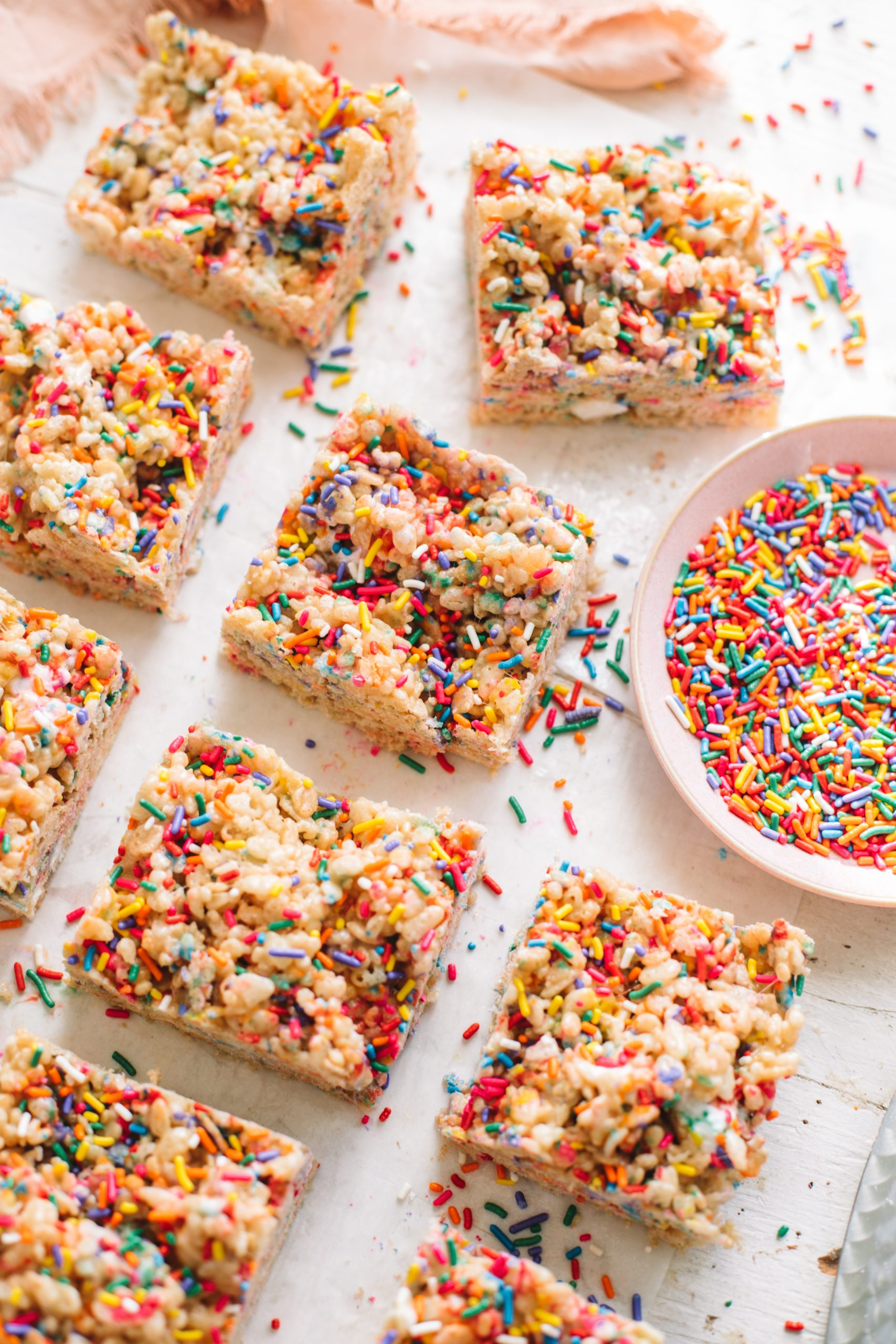 Rainbow sprinkle rice krispie treats with a pink bowl of rainbow sprinkles.