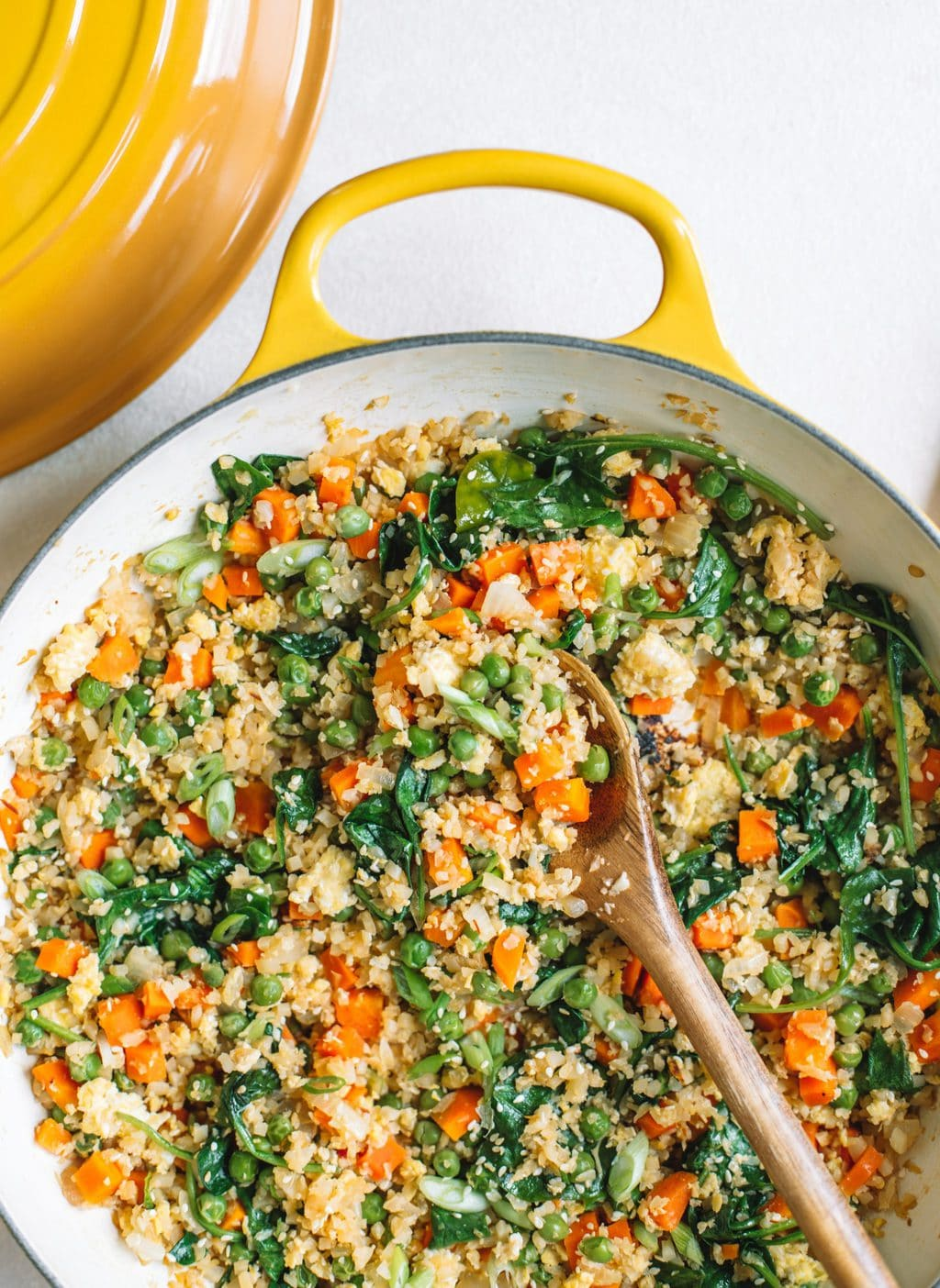 Cauliflower fried rice in a yellow skillet with a wooden spoon scooping a serving out.