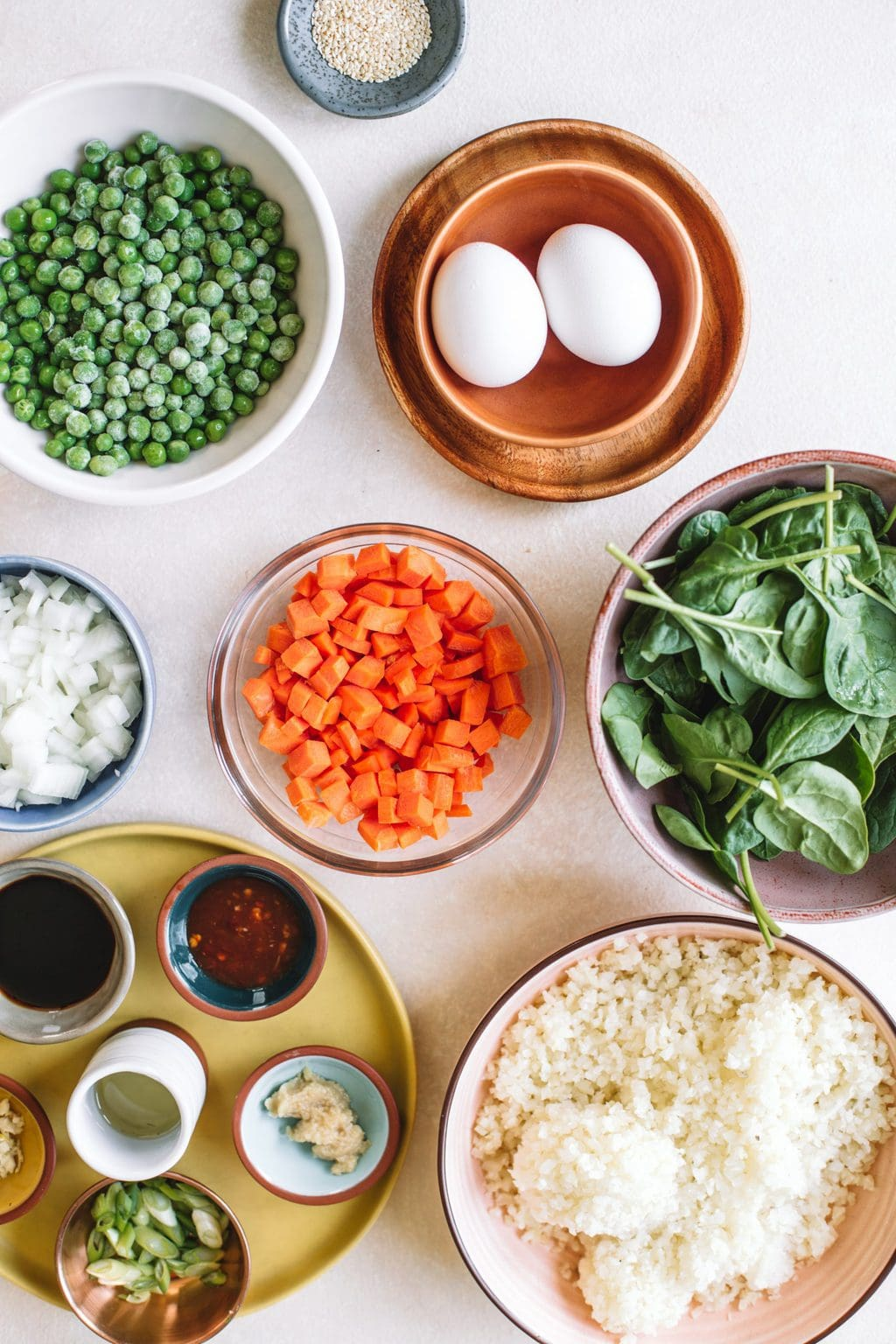 Ingredients in different sized bowls for cauliflower fried rice.