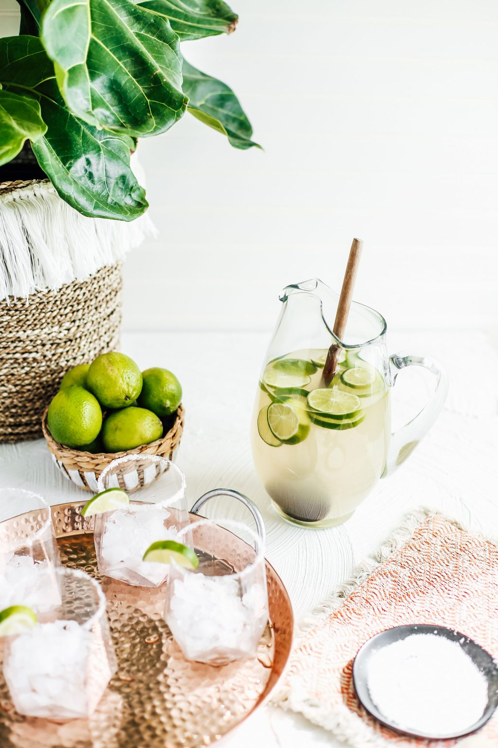 A large pitcher of margaritas with glasses rimmed with salt and lime wedges.