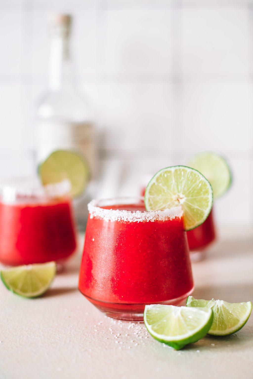 Frozen strawberry margarita in a clear, low ball glass garnished with a lime wheel.