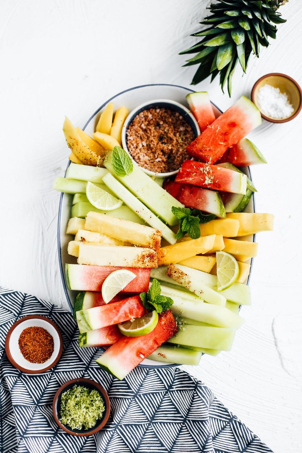 Honeydew, watermelon, pineapple and mango spears on an oblong platter with a bowl of chili lime seasoning.