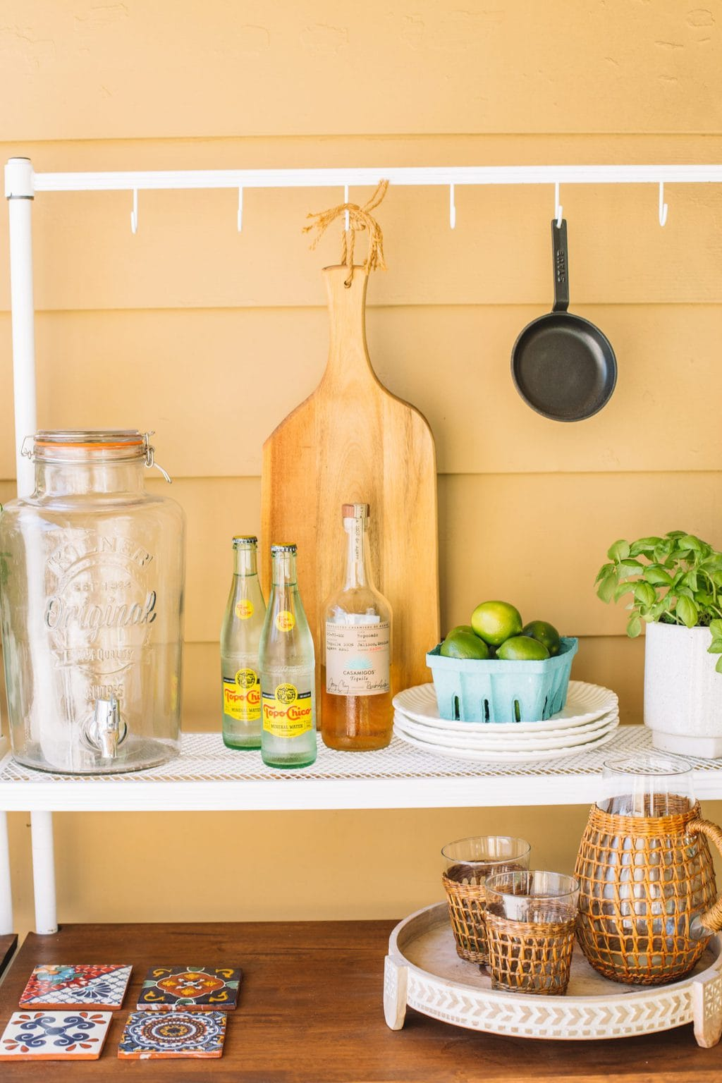 An outdoor patio buffet setup with a drink dispenser, sparkling water, tequila, limes and outdoor plates.