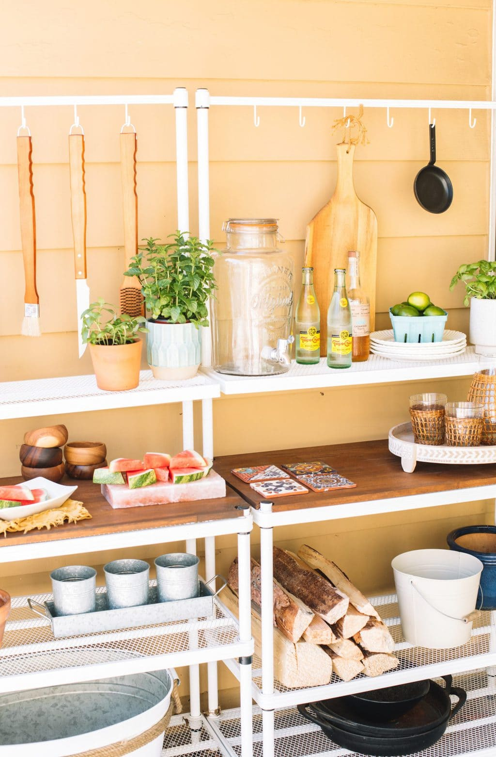 An outdoor patio buffet setup with bbq tools, plates, cups, planters and firewood.