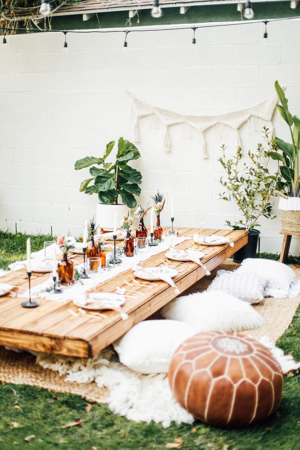 A dinner party setup in the middle of the backyard with plates, glassware and pillows as seats.