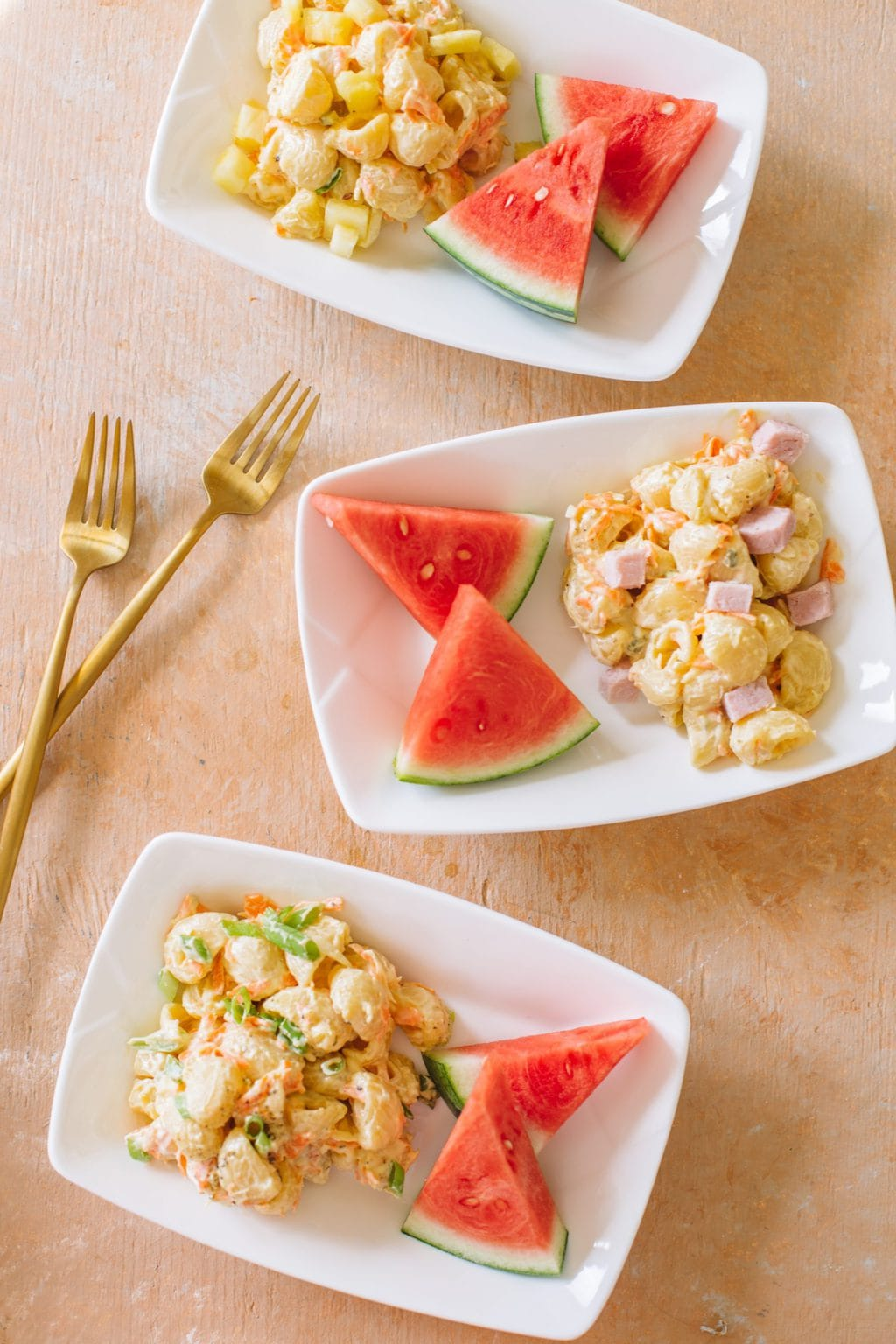 Macaroni salad served on small white dishes with watermelon pieces.