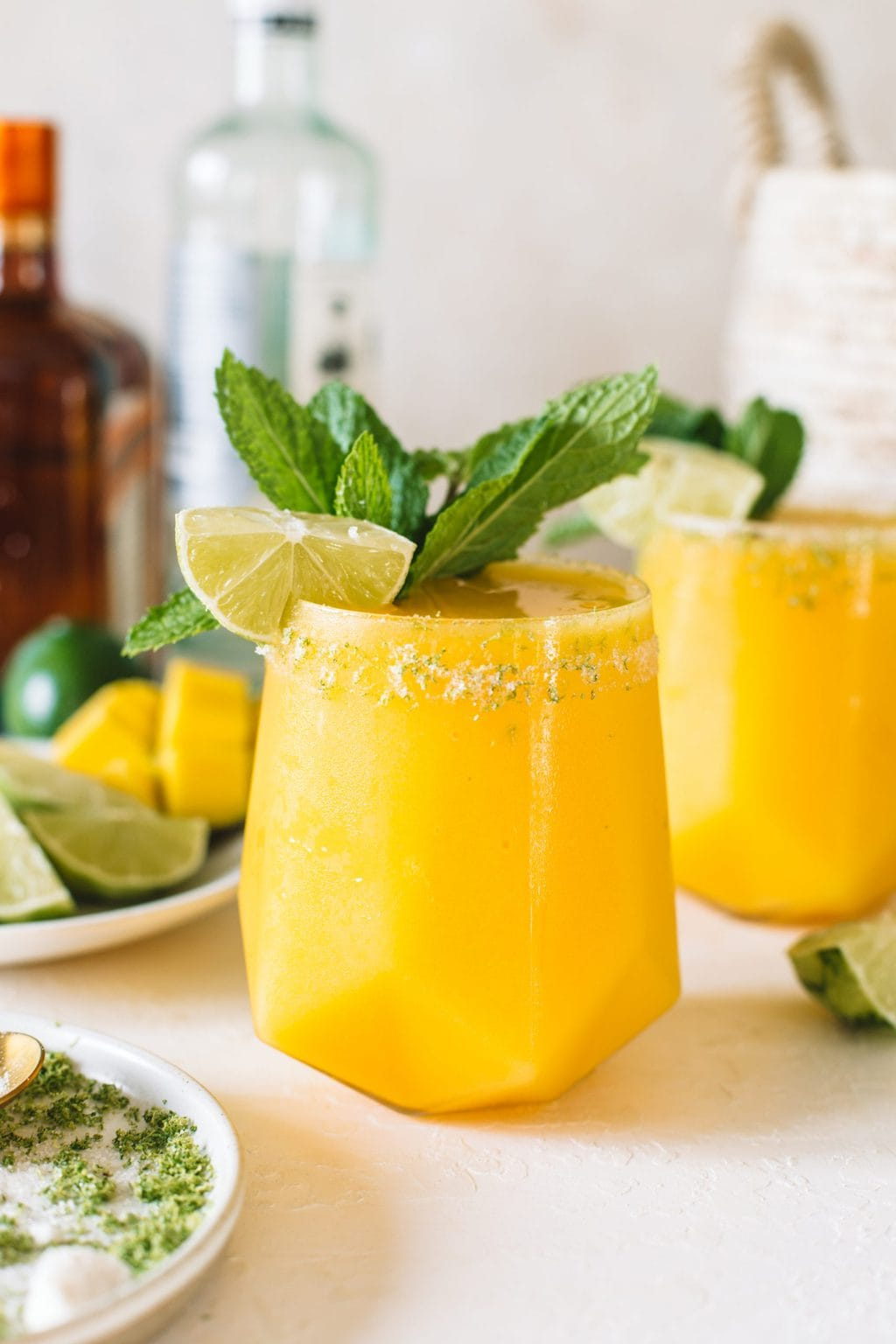 A short glass filled with mango daiquiri and topped with a fresh lime wedge and mint sprig.