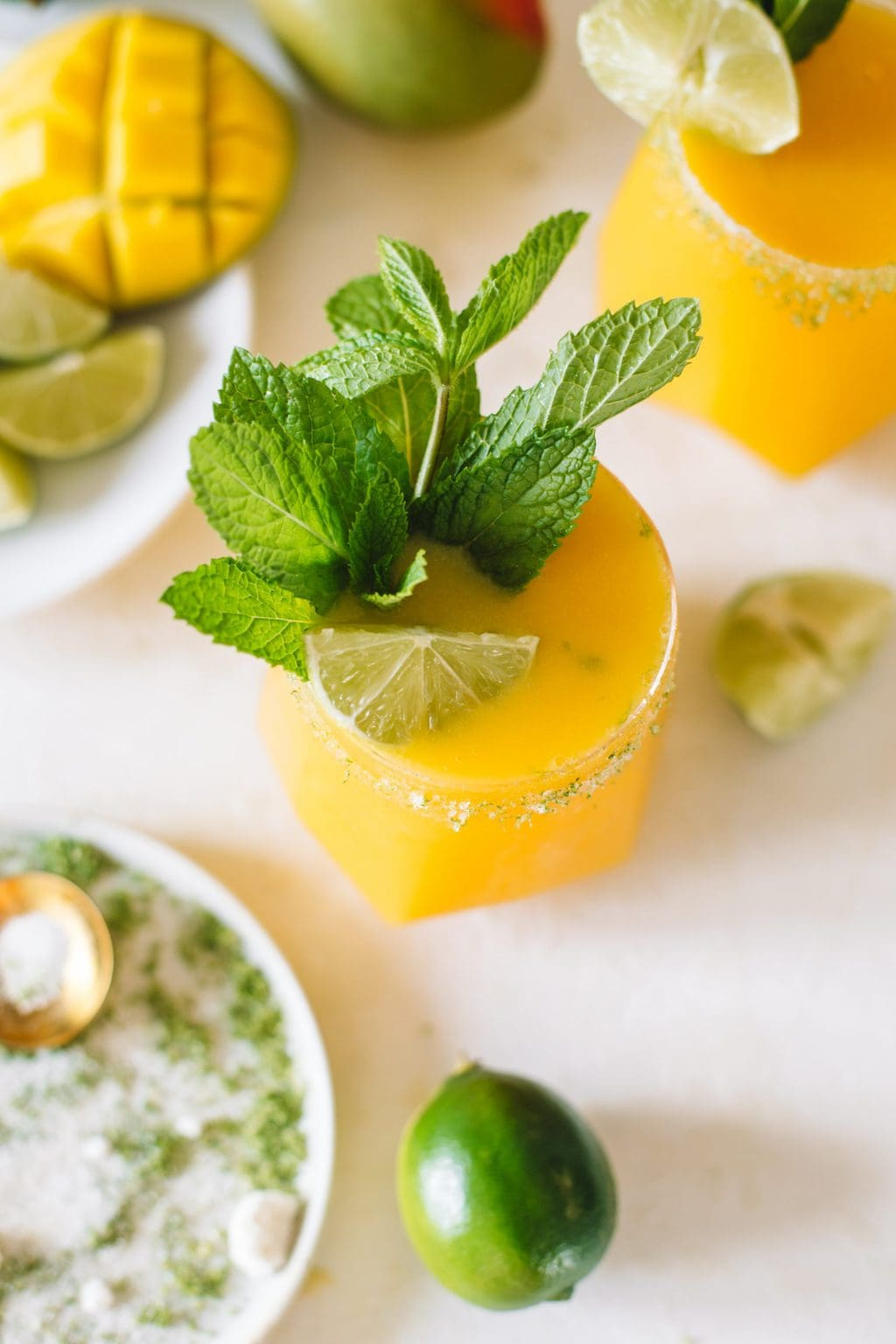 A frozen mango daiquiri with a fresh mint sprig and a lime wedge.