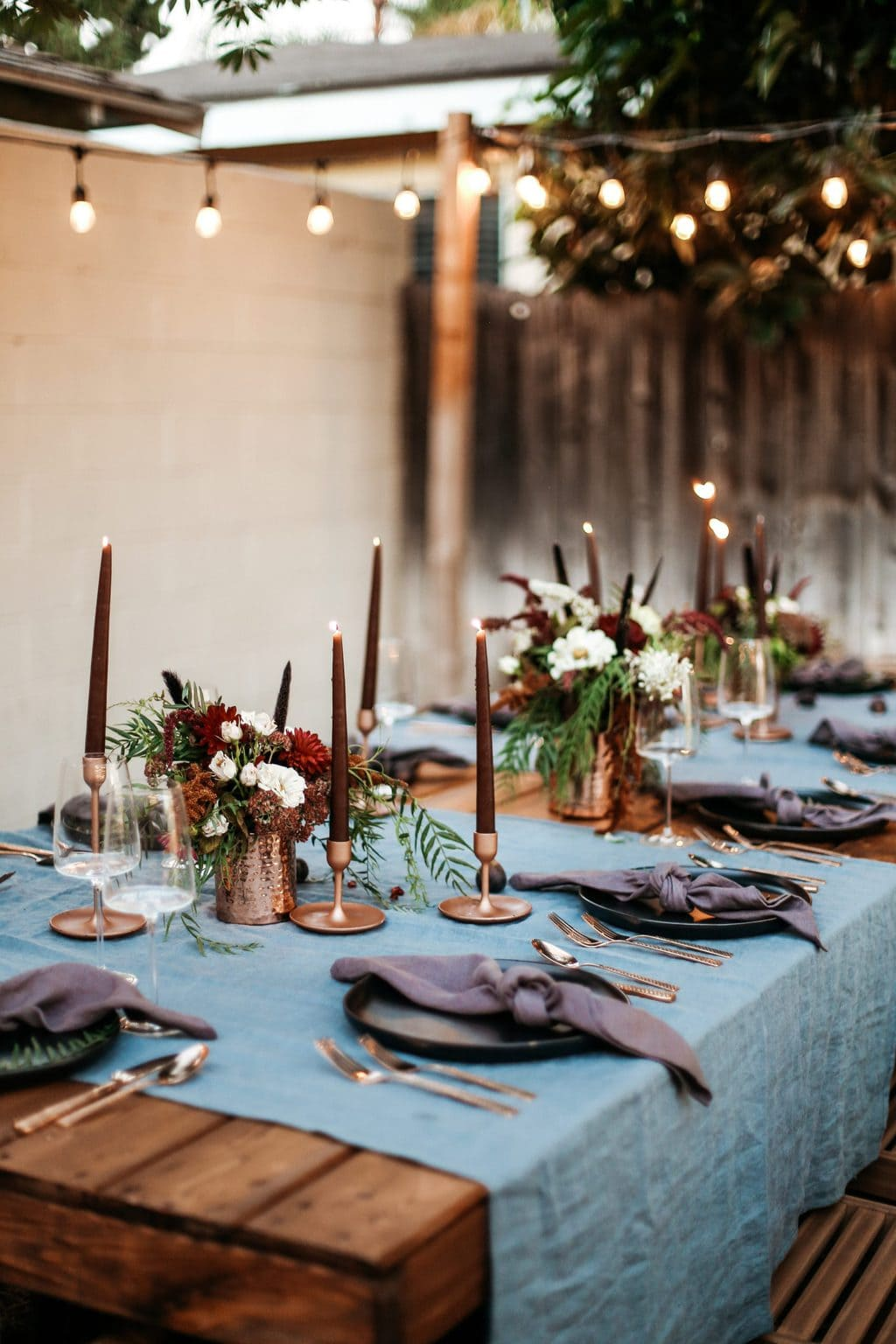 A moody dinner party set up with taper candles and string lights lit up.