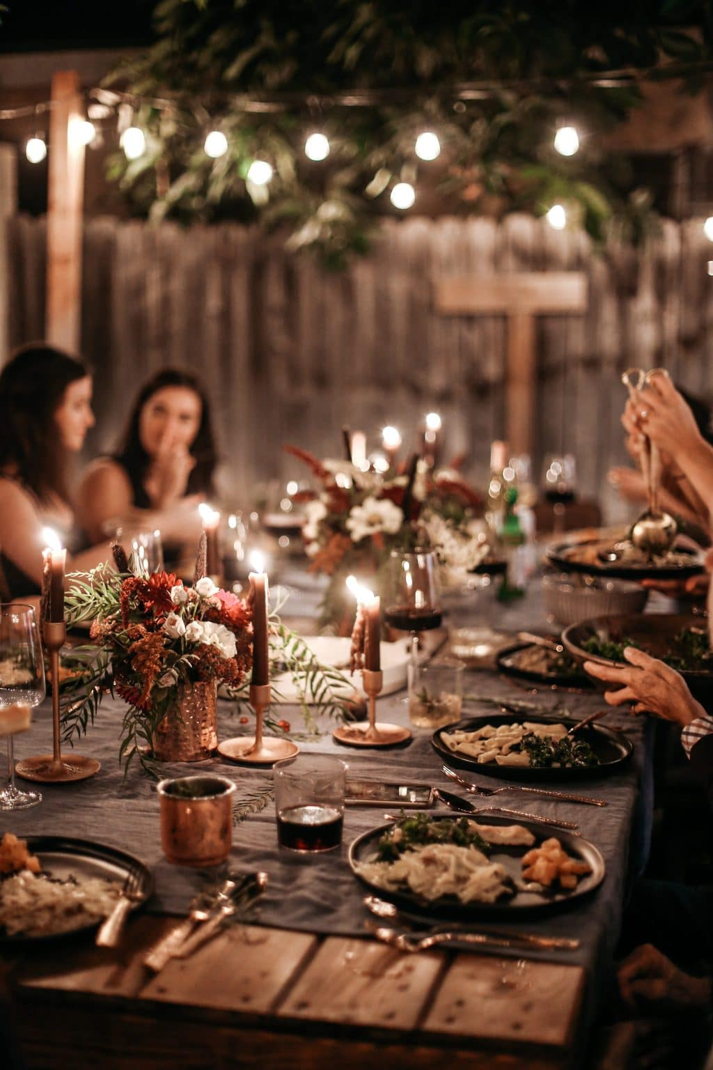 A dinner party at night with twinkle lights turned on overhead.