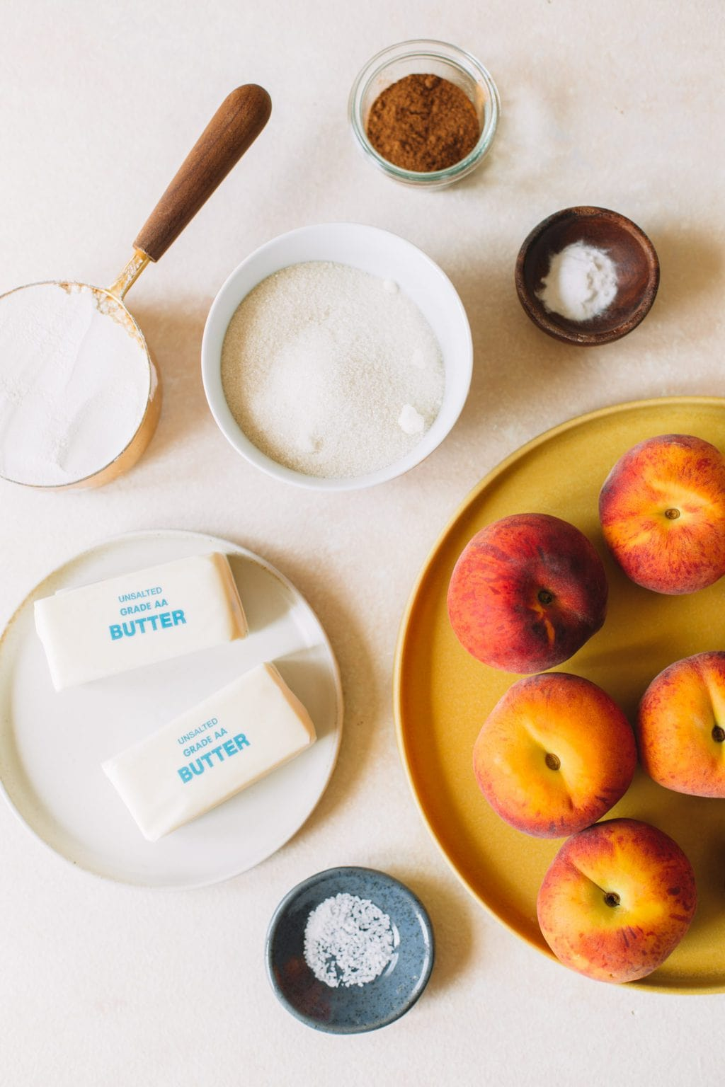 Ingredients in small bowls for peach cobbler.