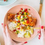 Salmon topped with pineapple glaze sitting on a bed or rice with pineapple salsa in a pink bowl.