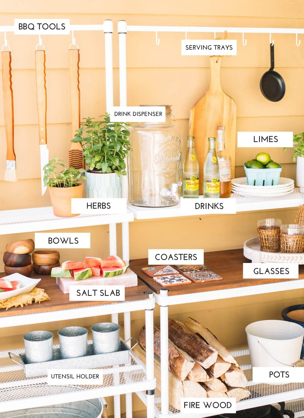 An outdoor buffet set up with a drink dispenser, herbs, glassware, plates, and a utensil holder.