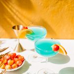 two blue curacao drinks in coupe glasses with orange slice and bowl of cherries