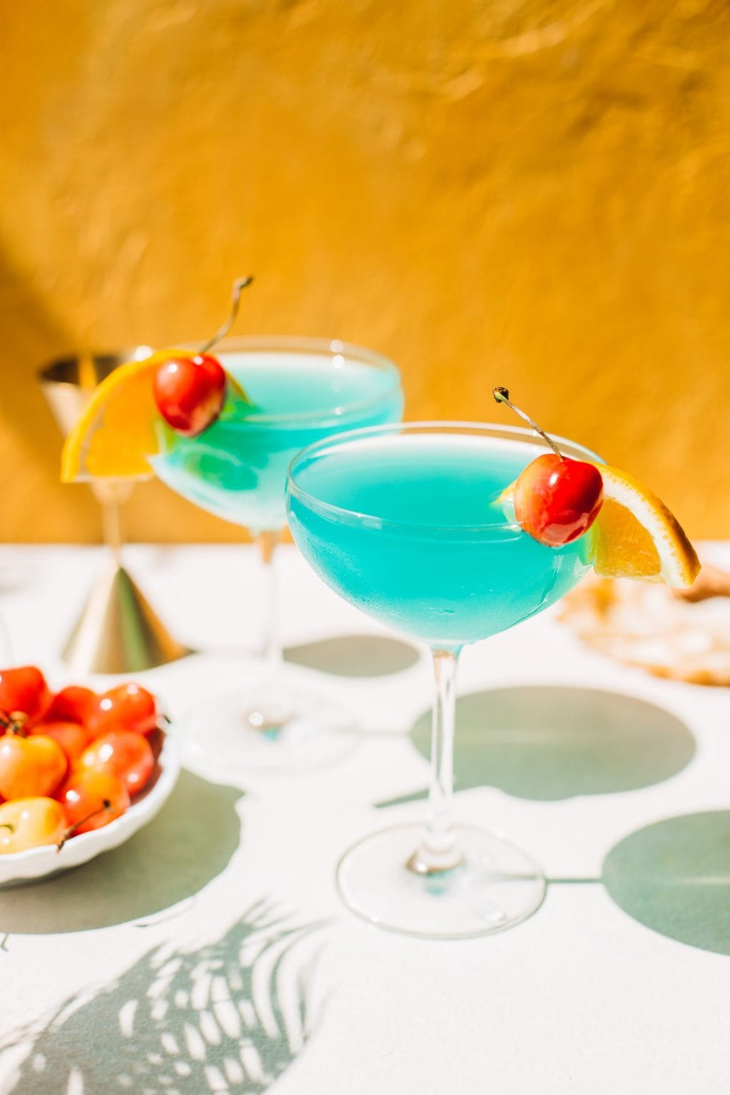two blue lagoon cocktails in coupe glasses with cherries and orange slices