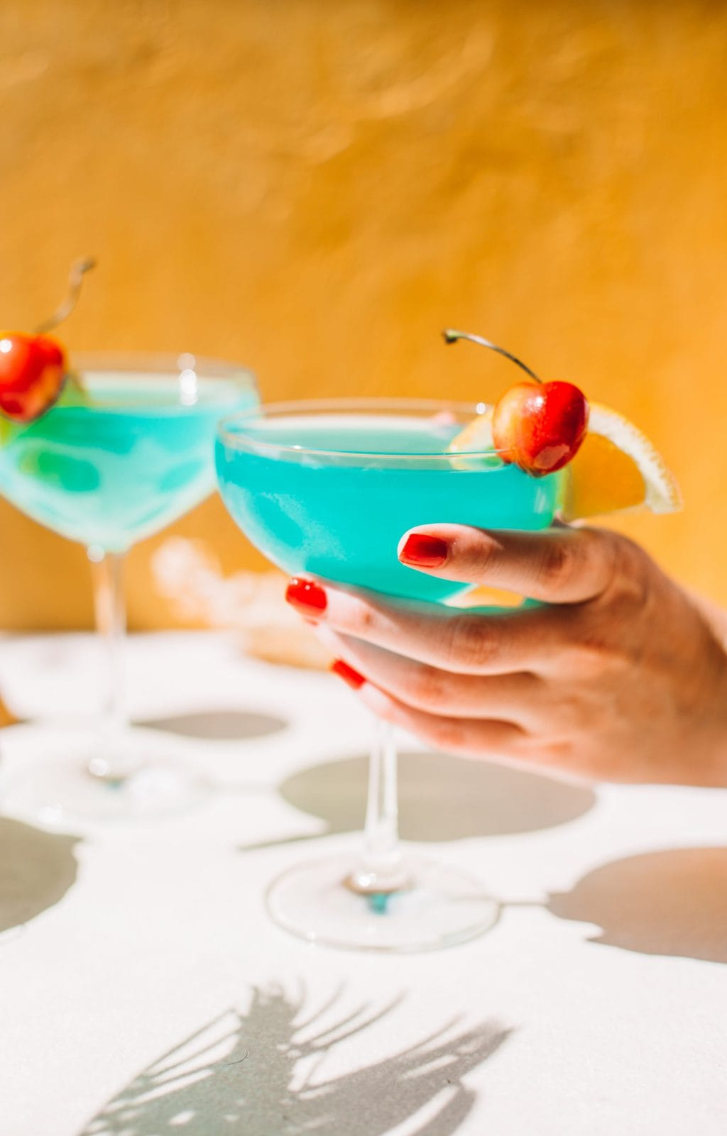 hand holding blue lagoon cocktail in coupe glass with blue caracao drink in background