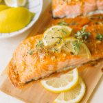 glazed salmon fillets with lemon slices and fresh thyme on cedar plank
