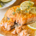 flaked salmon fillet topped with lemon slices and fresh thyme on cedar wood plank