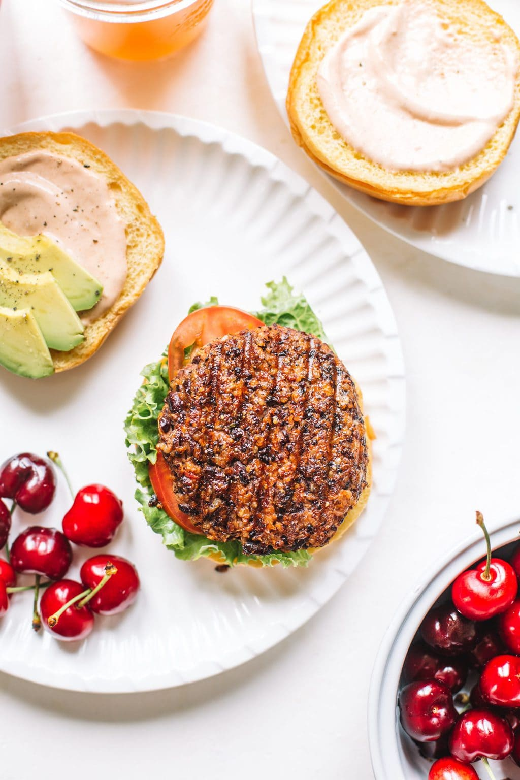 chipotle black bean burger patty on bun with lettuce, tomato, sauce on white plate