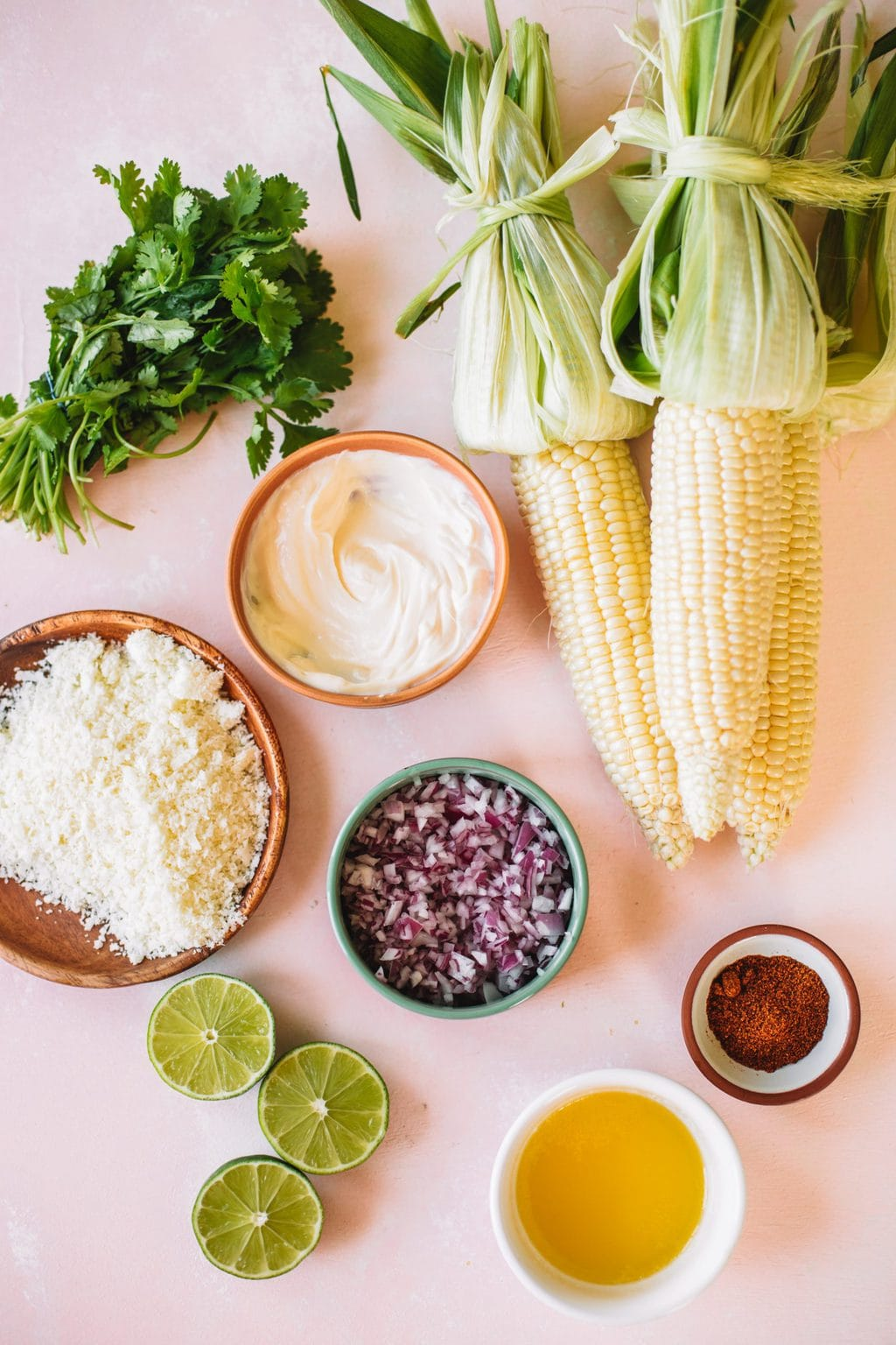 Cotija cheese, mayonnaise, red onion, limes, corn, chili powder, and melted butter.